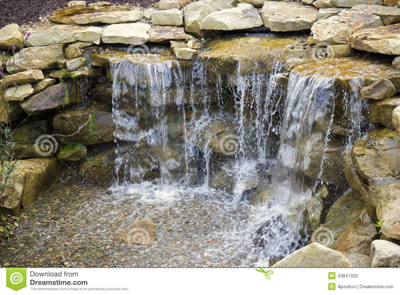manmade waterfall pours over pebbles stock photo image 43841333