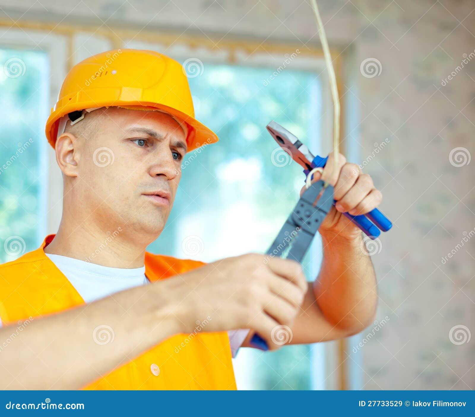 Mann arbeitet mit elektrischen Drähten