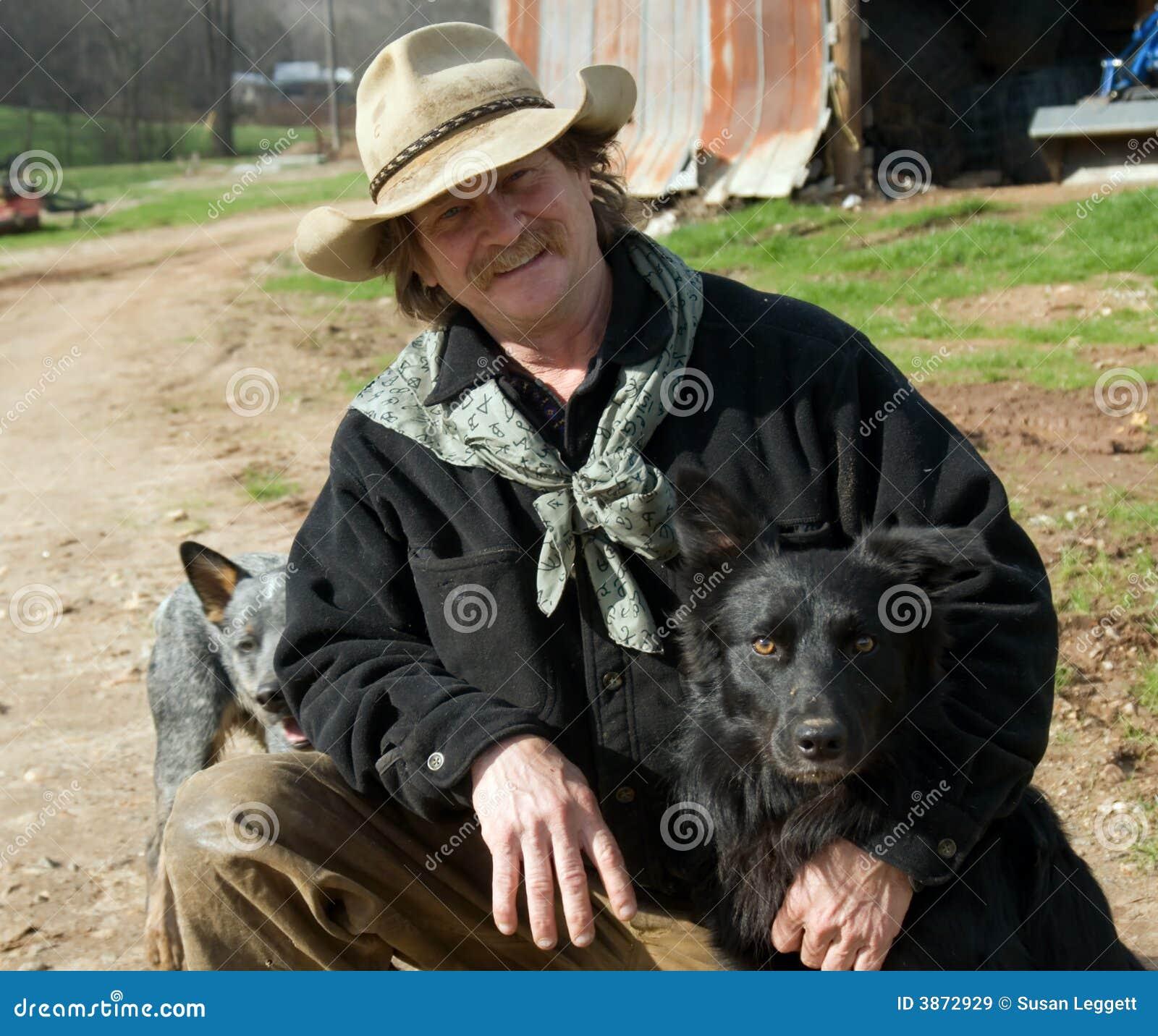 Mann auf Bauernhof mit seinen Hunden