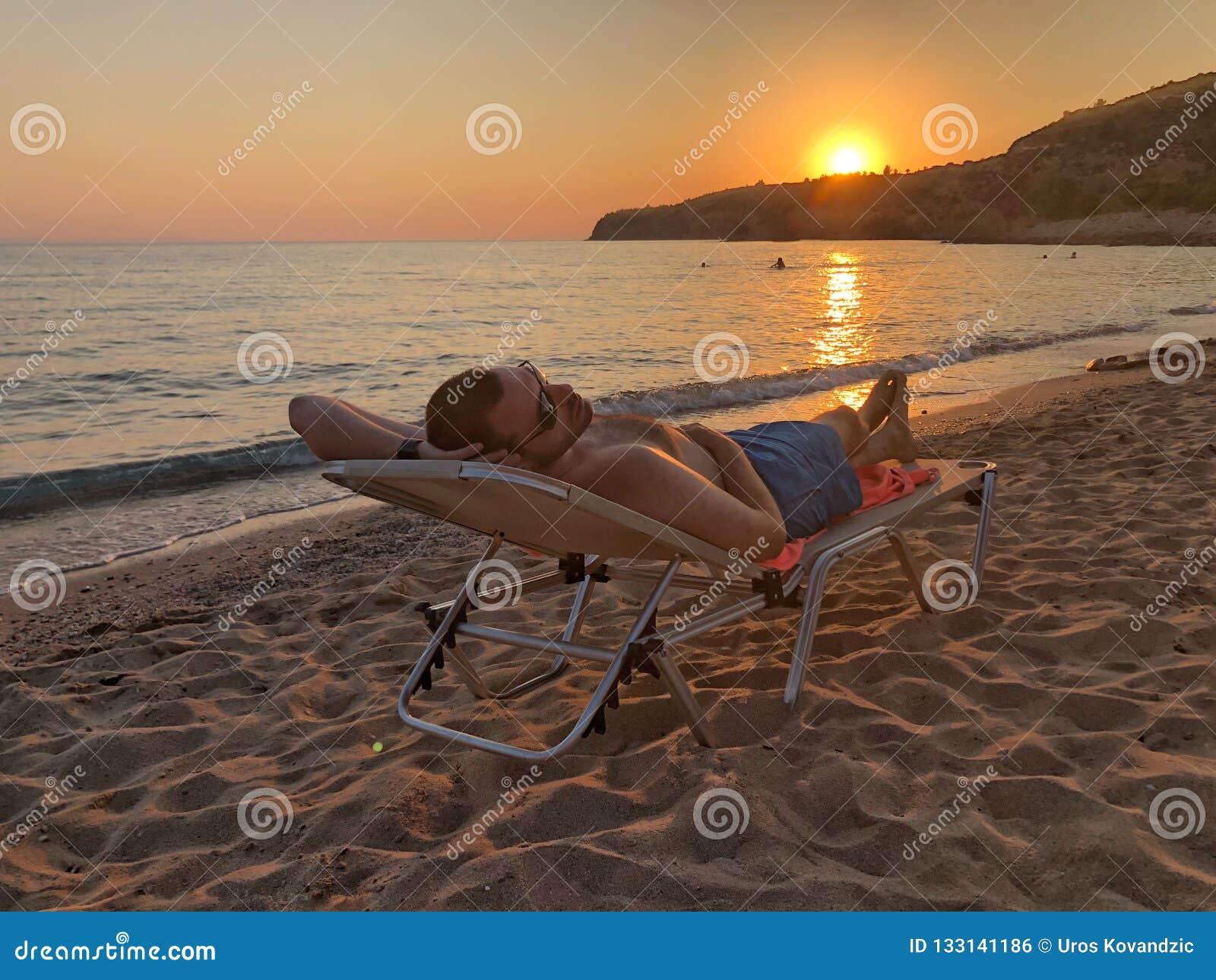 Mann auf dem Strand am Sonnenuntergang