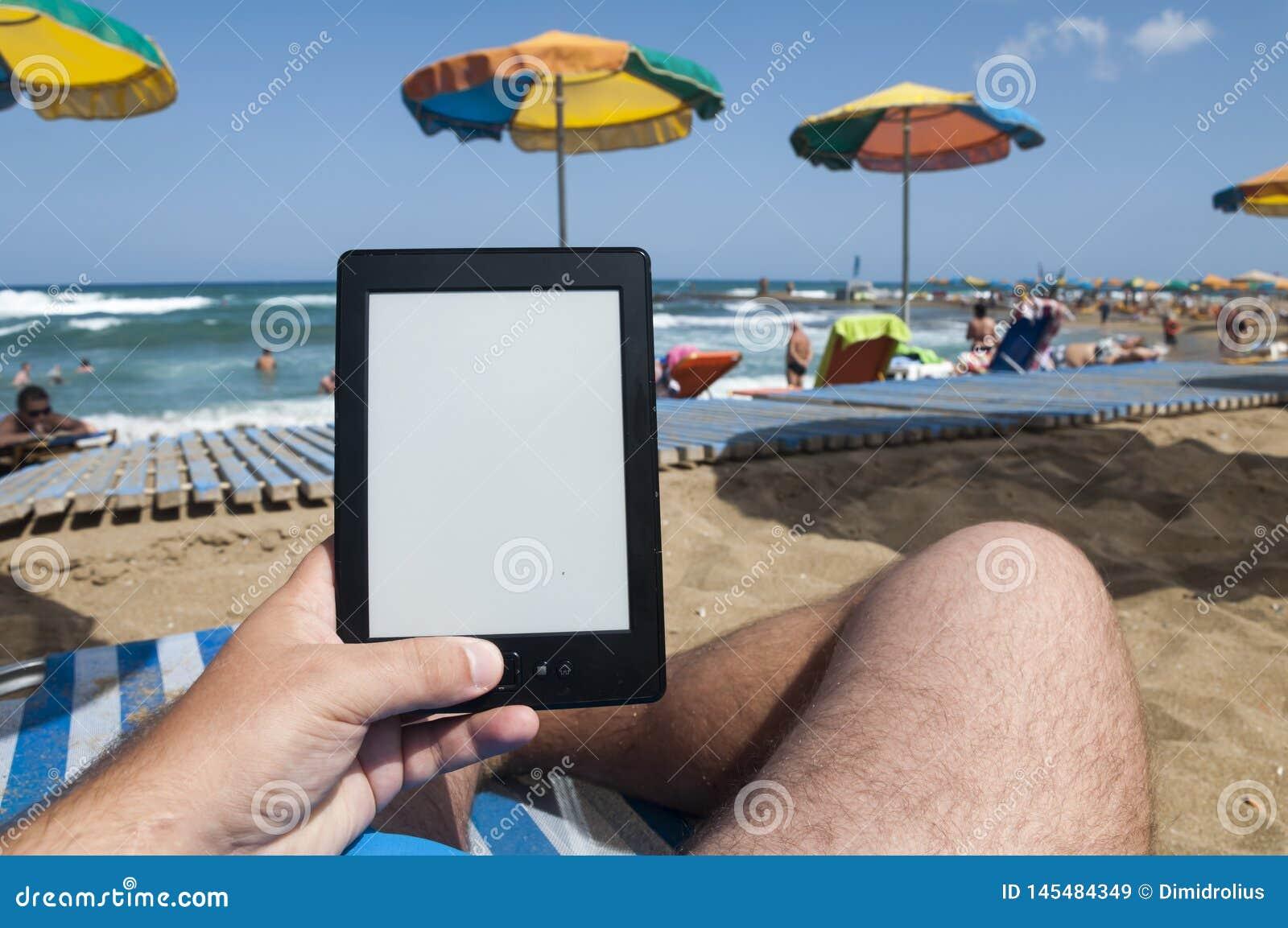 Mann auf den Strandhänden, die ebook Leser halten