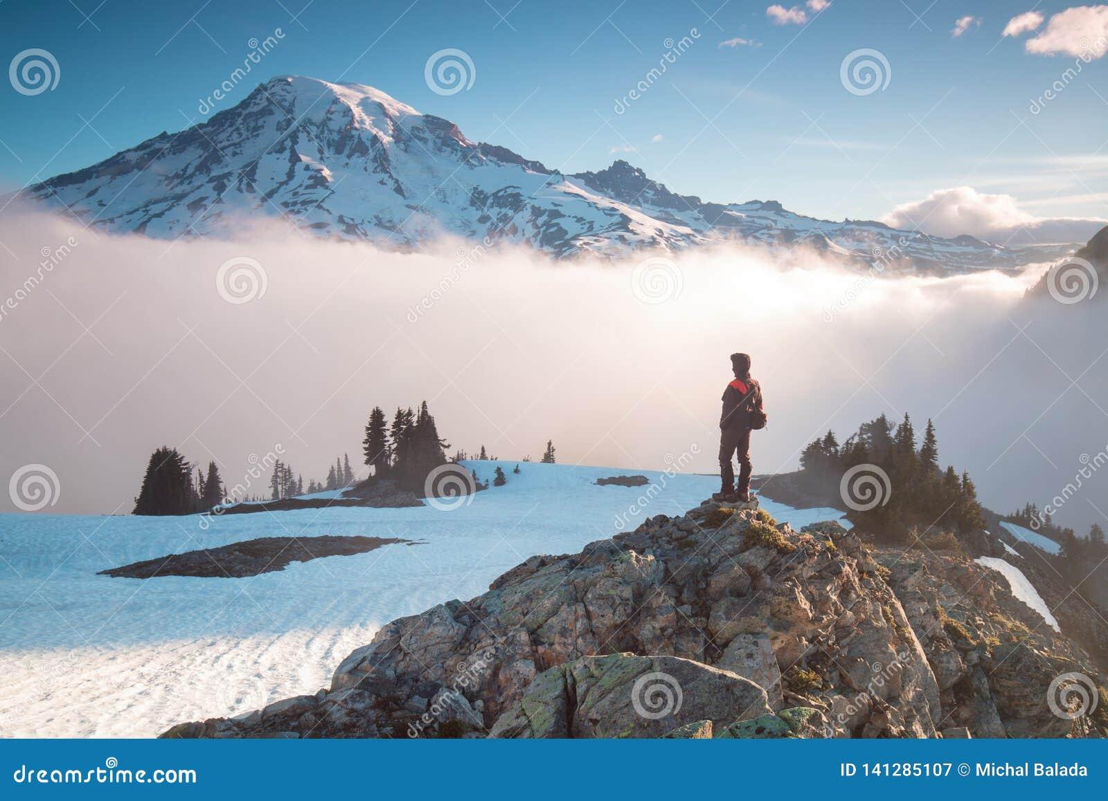 Mann auf der Bergspitze, die auf Gebirgstal mit tiefen Wolken buntem Sonnenaufgang im Herbst in Berg-Rainier National-Park betrac
