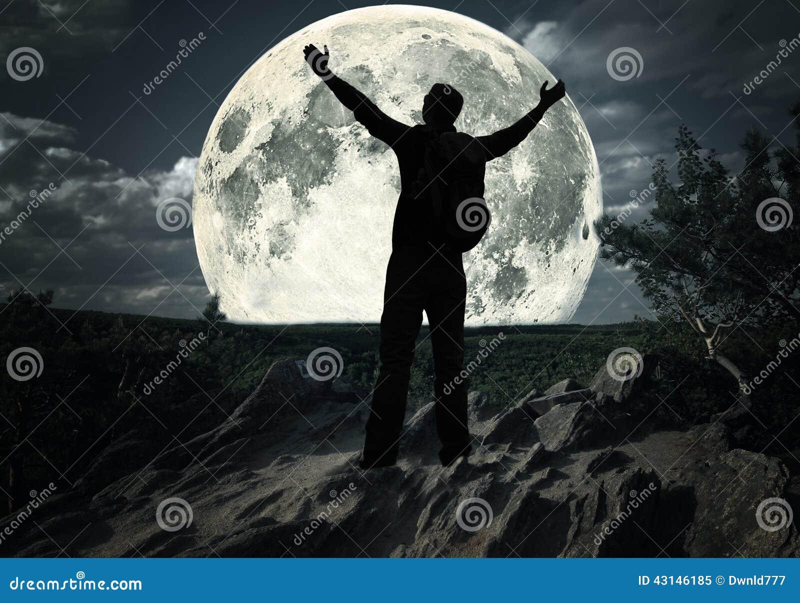 Mann auf die Oberseite des Berges den Mond betrachtend
