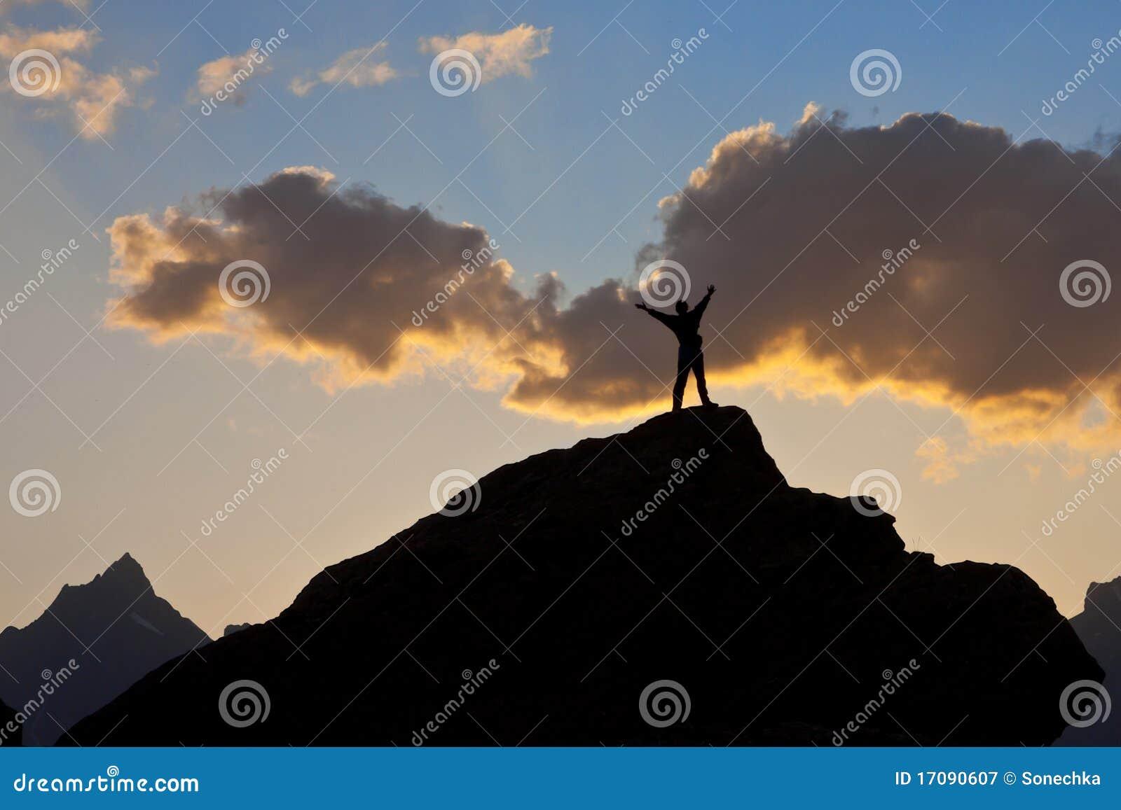 Mann auf die Oberseite einer Klippe am Sonnenuntergang