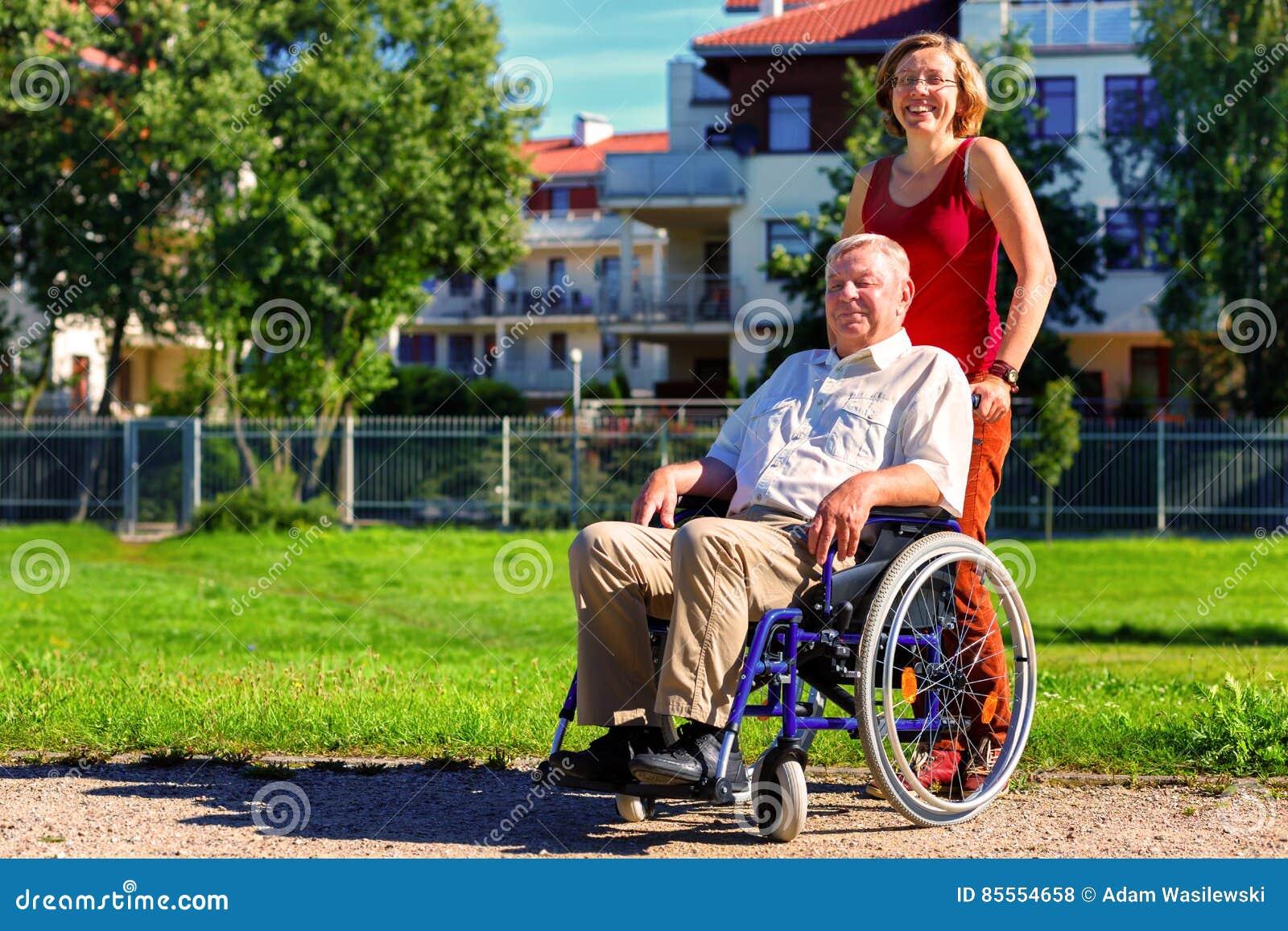 Mann auf Rollstuhl mit junger Frau