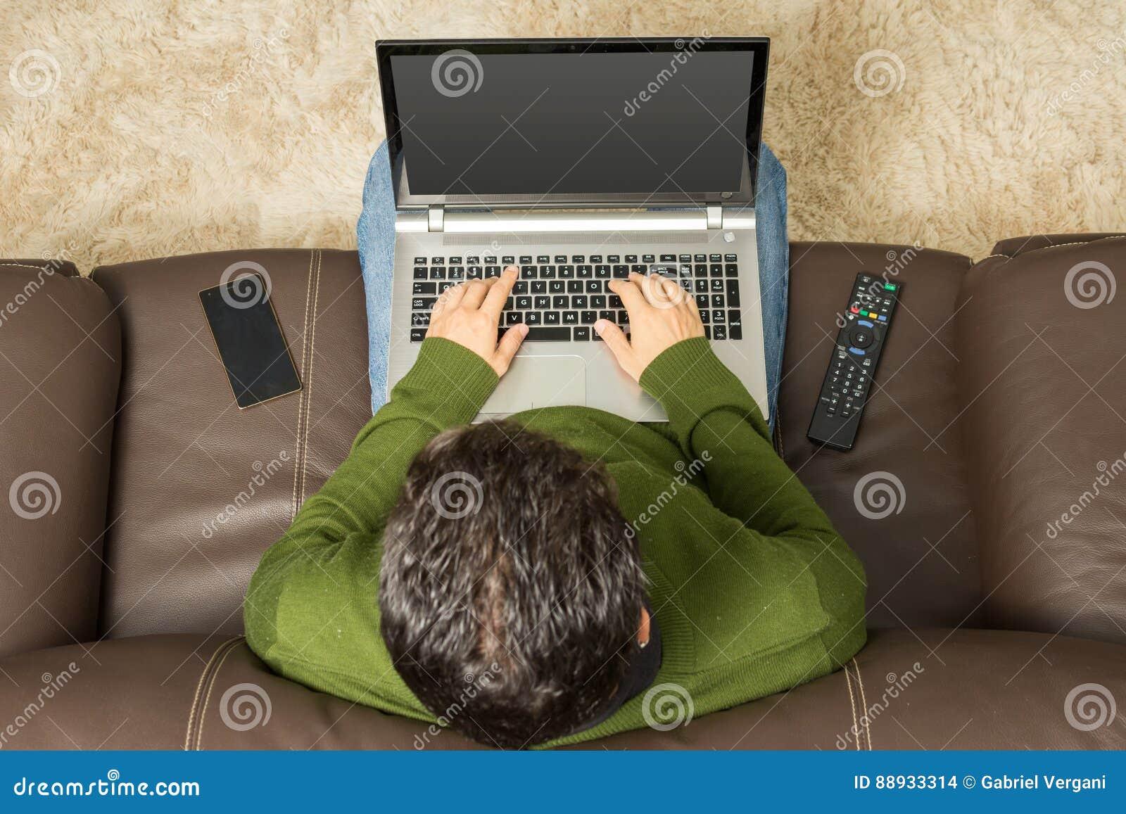 Mann benutzt Laptop auf Sofa Obenliegende Ansicht, braune Couch