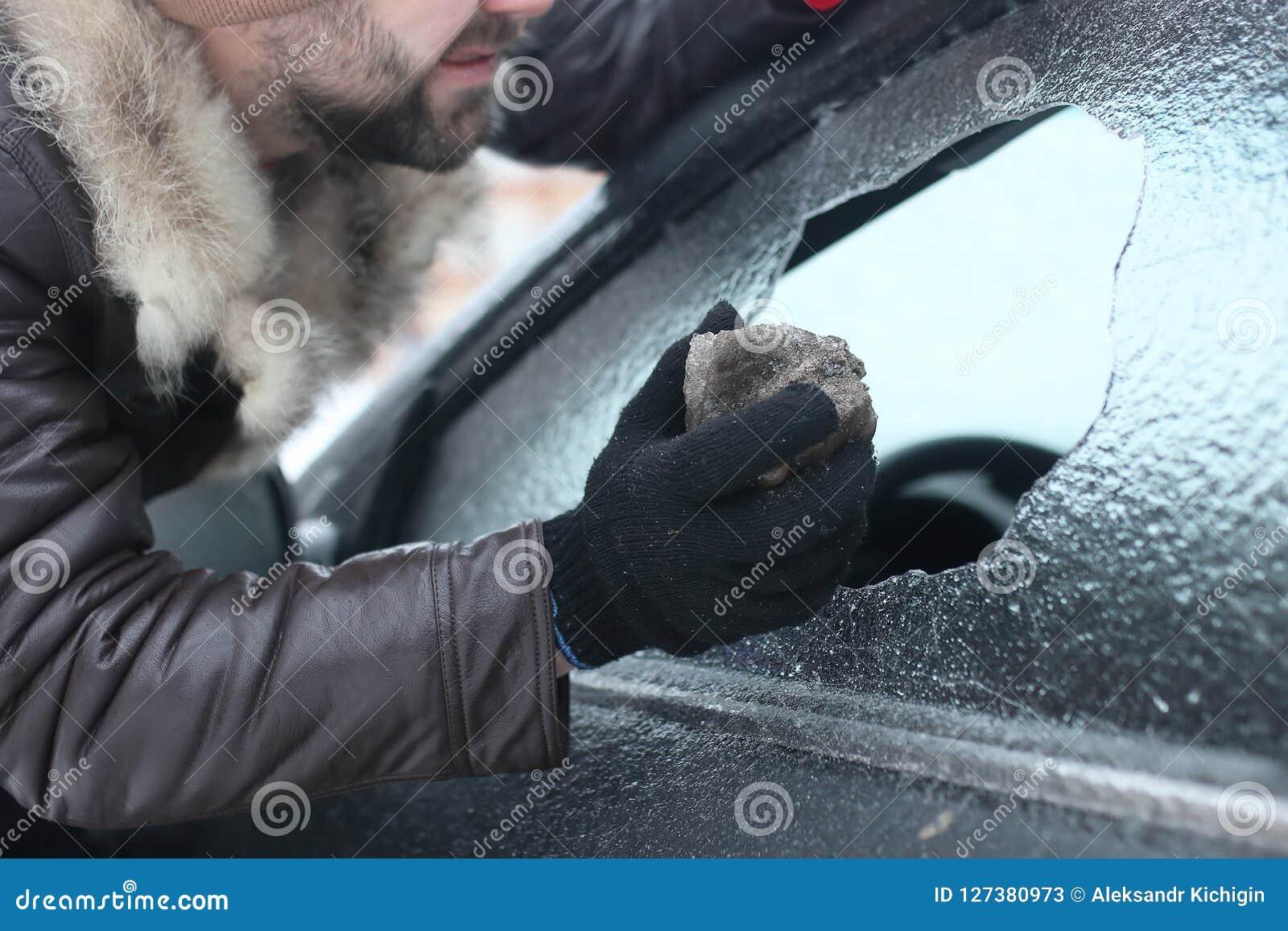 Mann brach das Glas des Autos ein kleiner Stein