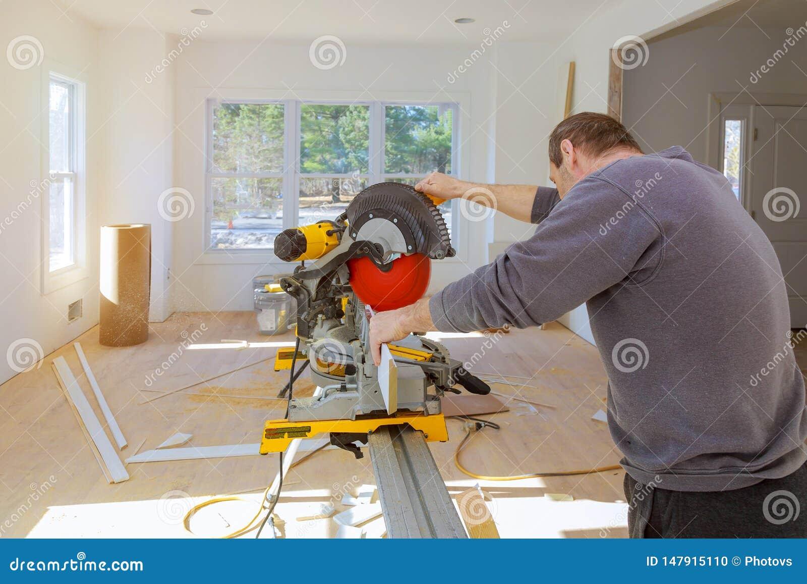 Mann in den Beruftischler-Erbauersägen mit Kreissäge ein niedriges Formteil der hölzernen Ordnung