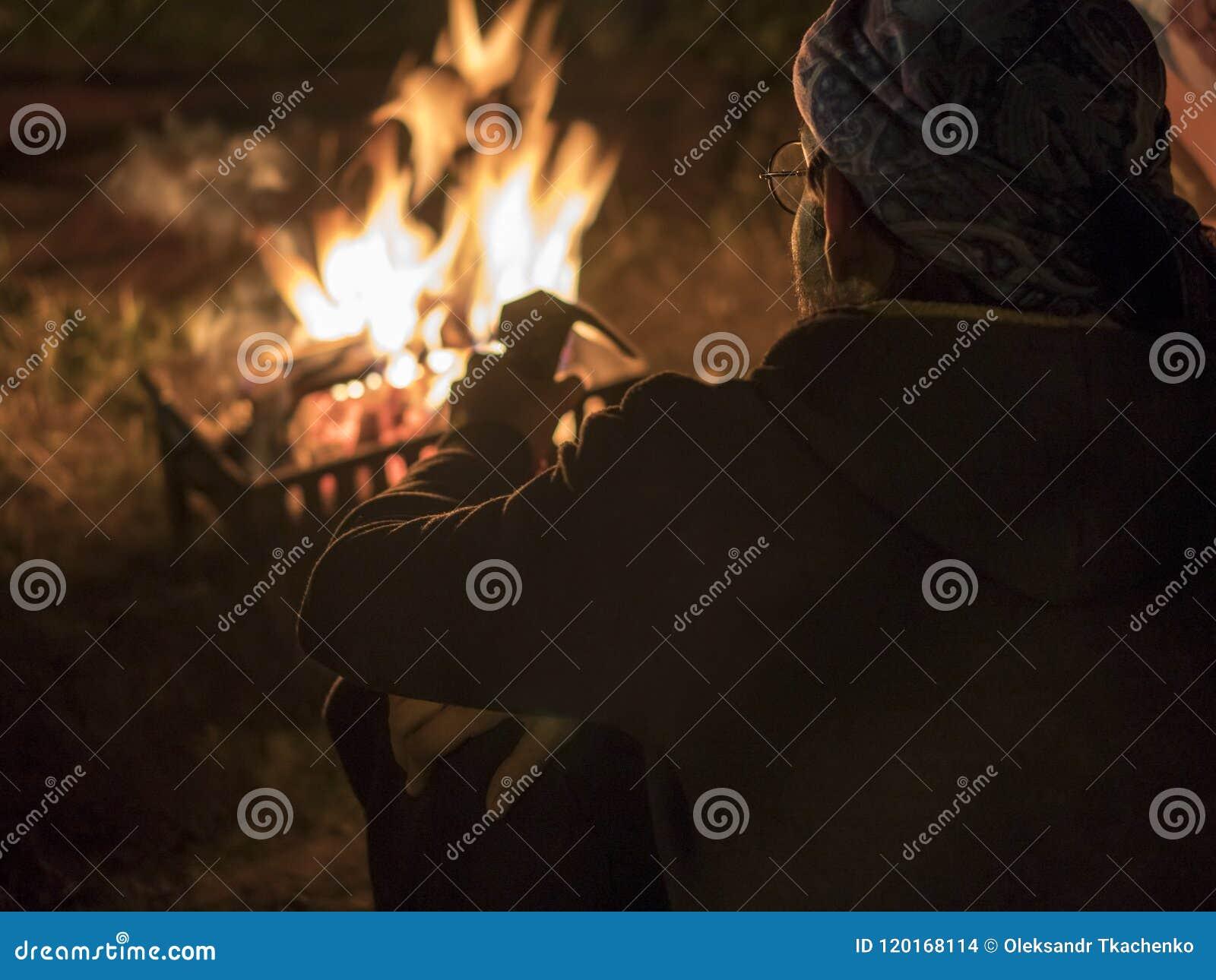 Mann in den Gläsern nahe dem Feuer nachts in altem Höhlen-Stadt Uchisar-Schloss in Cappadocia