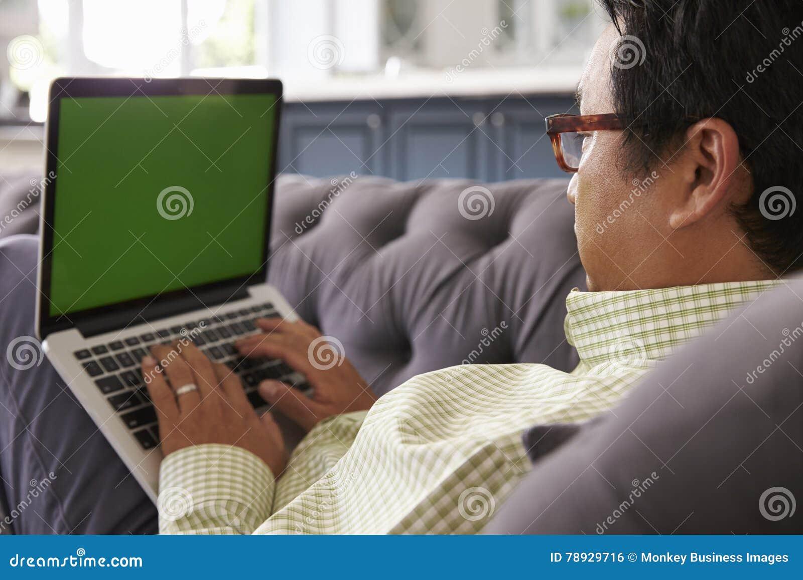 Mann, der auf Sofa At Home Using Green-Schirm-Laptop sich entspannt