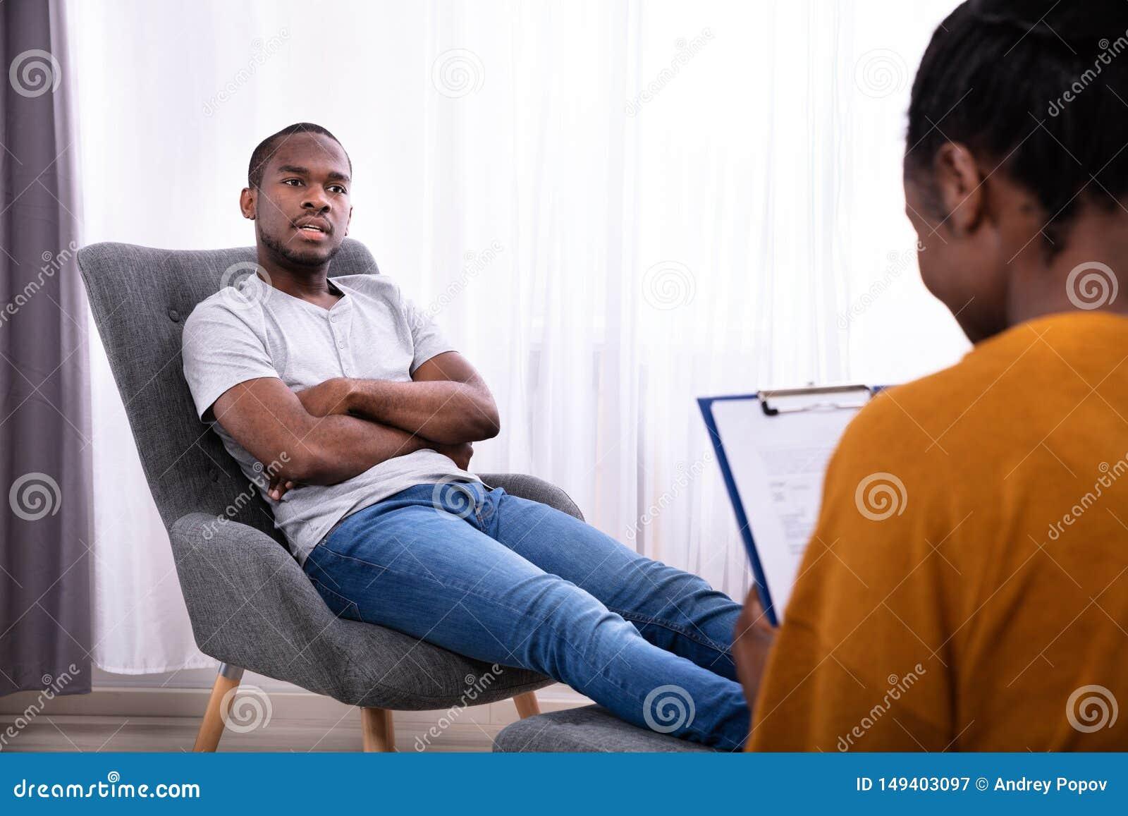 Mann, der auf Stuhl nahe Psychologen sitzt