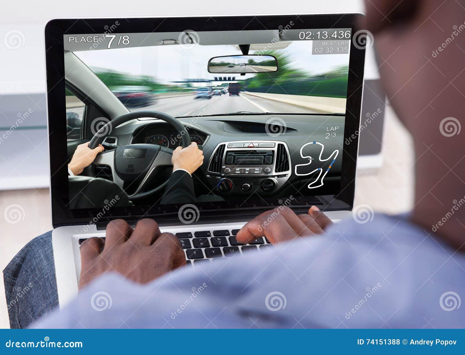 mann der auto spiel auf laptop spielt