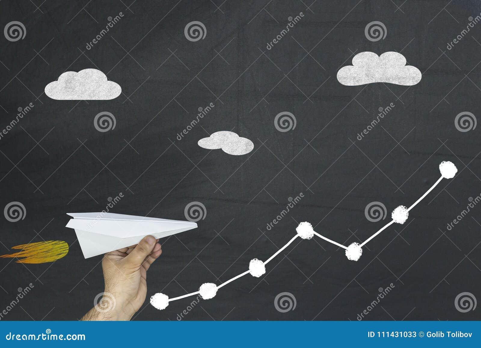 Mann, der das flache Fliegen des Papiers oben auf wachsendes Diagrammpfeildiagramm auf Tafel hält übergeben Sie den Holdingbleist