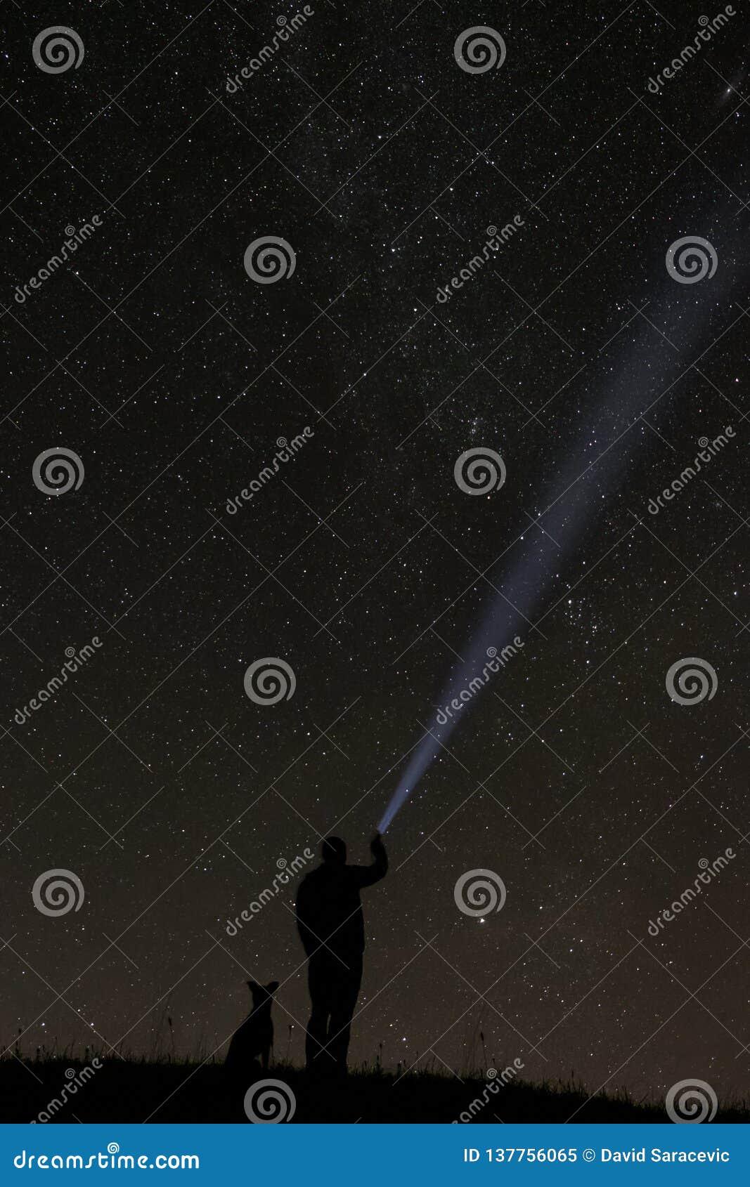 Mann, der die Sterne mit seinem Hund betrachtet
