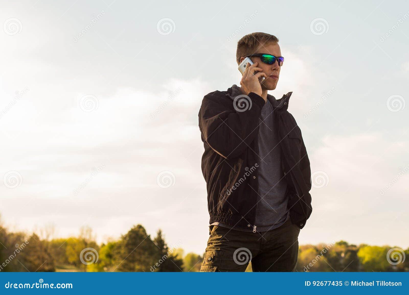 Mann, der draußen auf Smartphone spricht