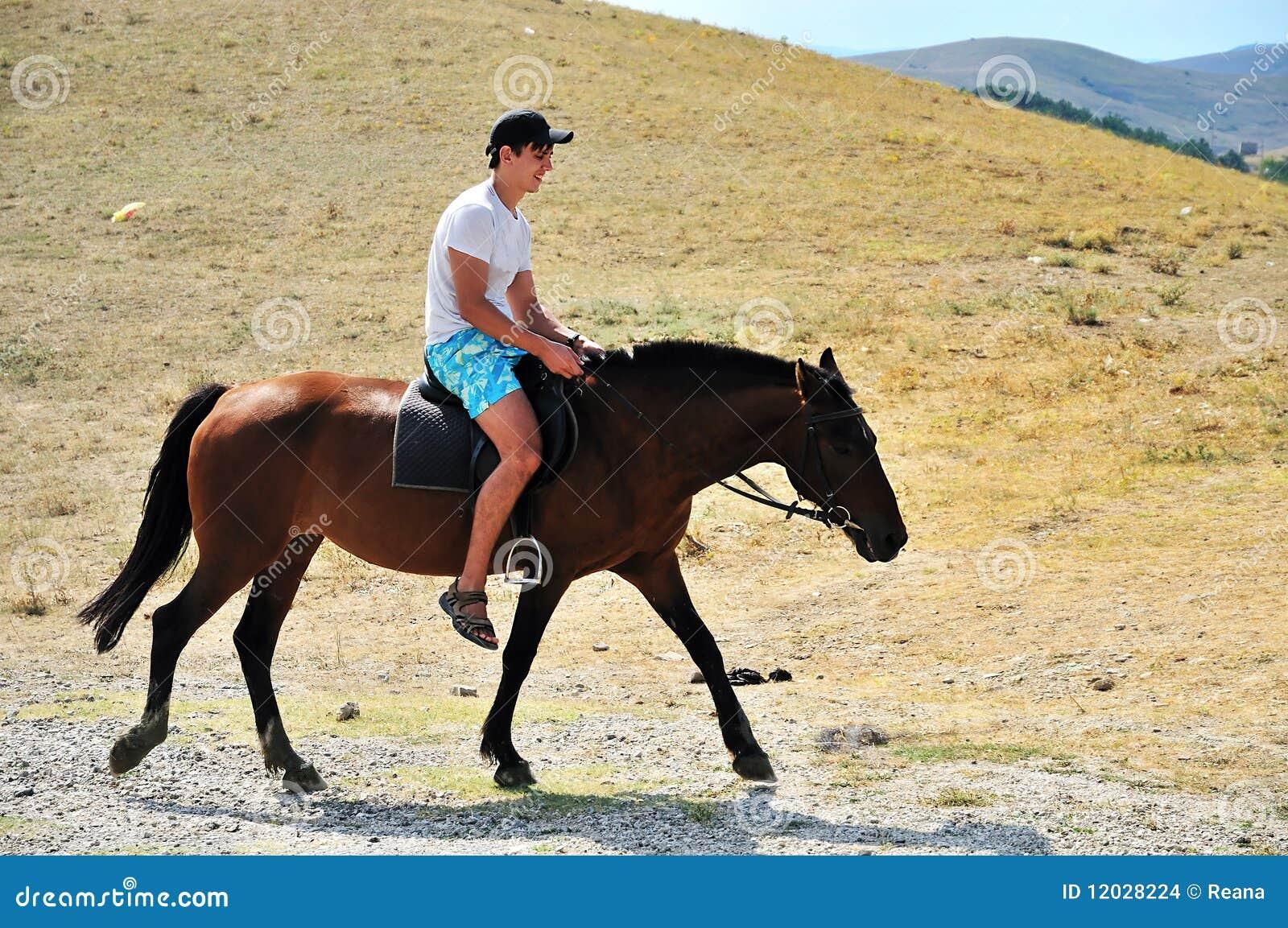 Mann, der ein Pferd reitet stockfoto. Bild von farbe