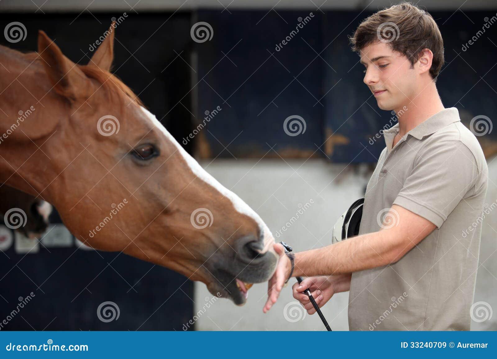 Mann, der ein Pferd streichelt