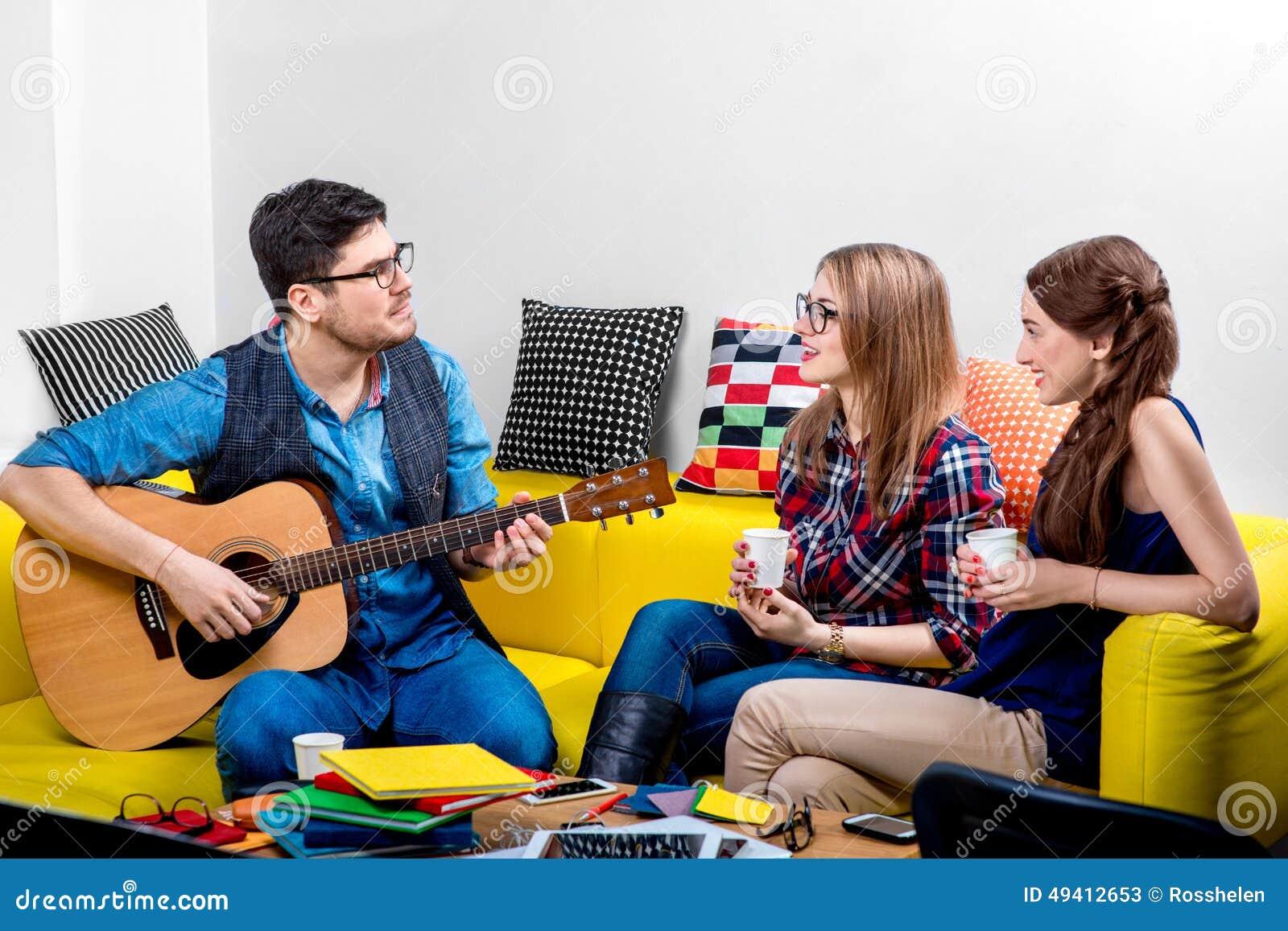 Download Mann, Der Eine Gitarre Mit Freundinnen Spielt Stockbild - Bild von frau, spaß: 49412653
