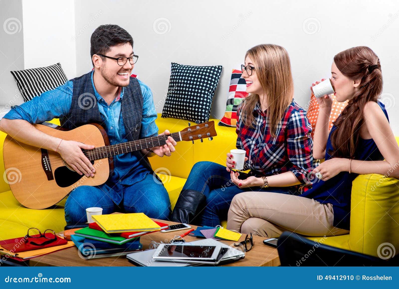 Download Mann, Der Eine Gitarre Mit Freundinnen Spielt Stockfoto - Bild von couch, freunde: 49412910