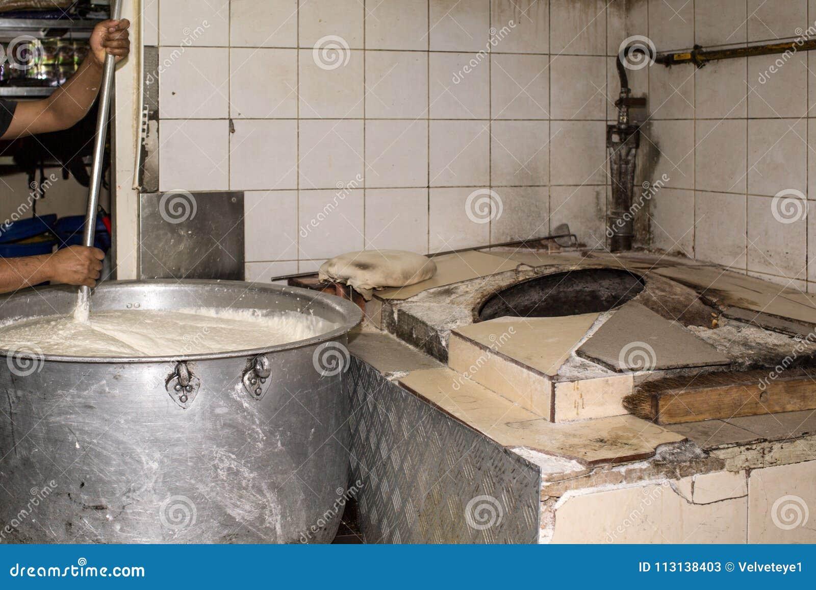 Mann, der in einem wirklichen Grungy schmutzigen Restaurant industriell u. in Comme kocht