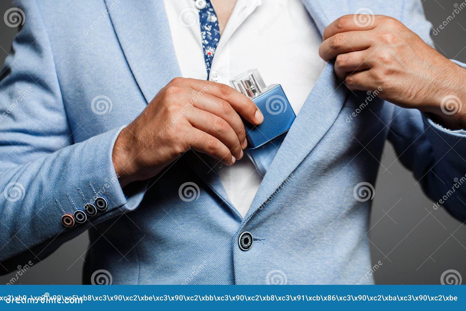 Mann, der Flasche Parfüm hält Männer parfümieren in der Hand auf Klagenhintergrund Gut aussehender Mann im Gesellschaftsanzug und