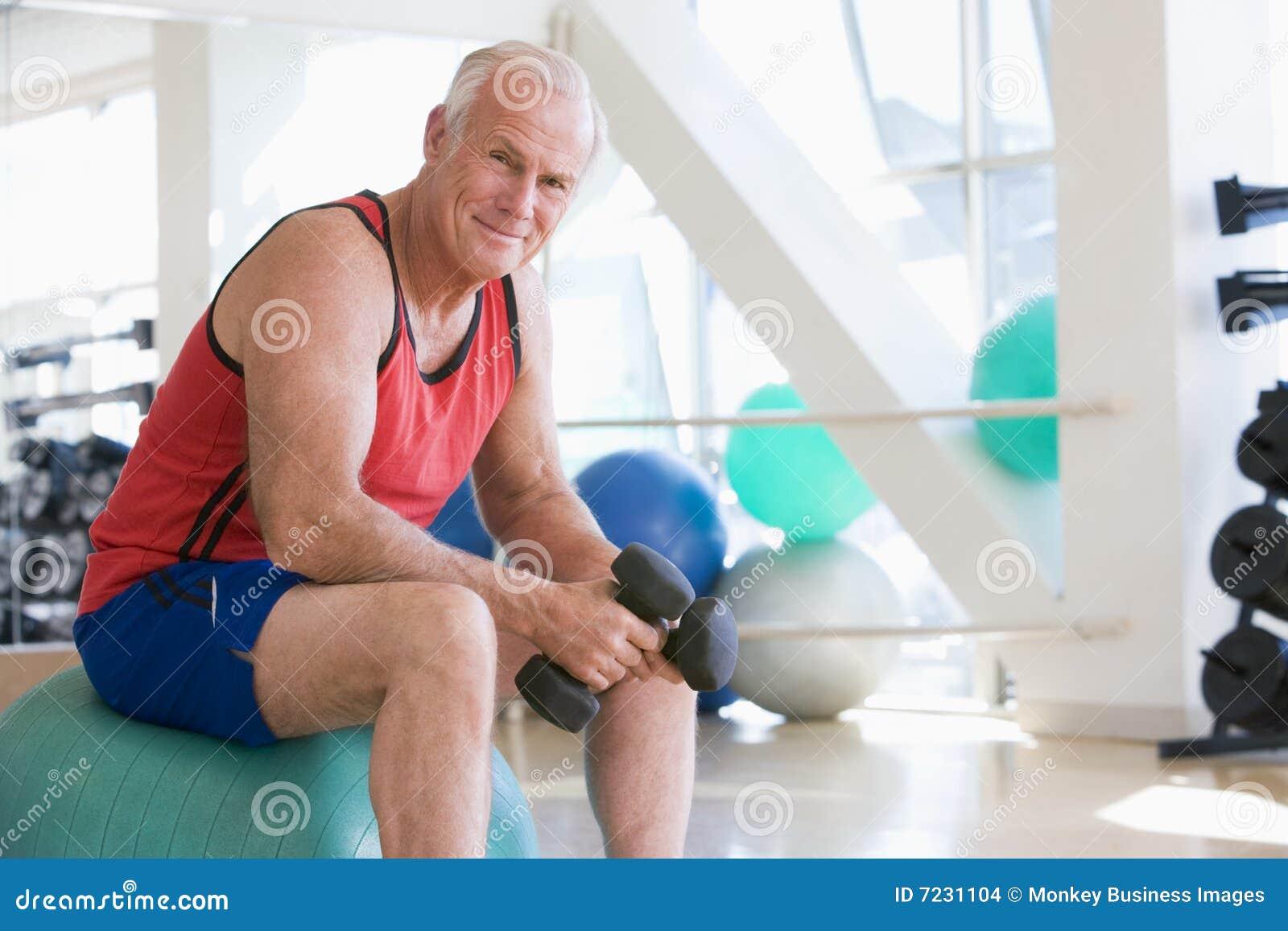 Mann, der Handgewichte auf Schweizer Kugel an der Gymnastik verwendet