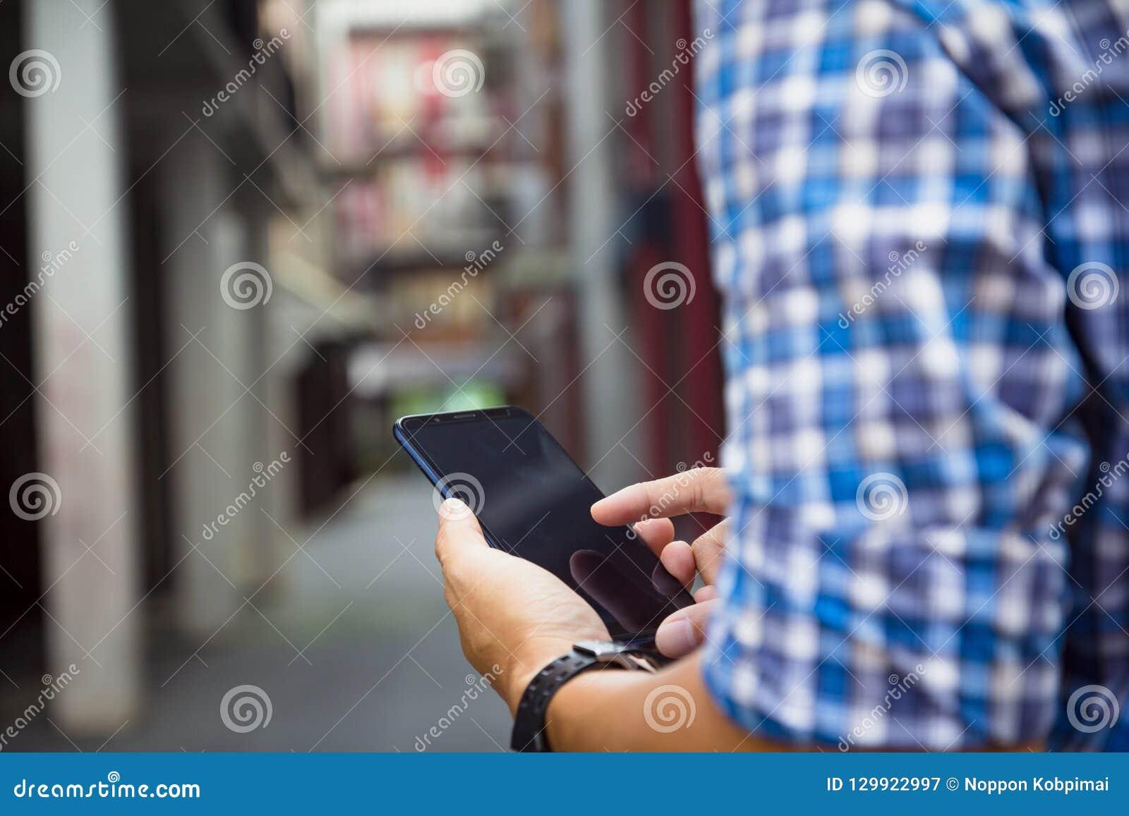 Mann, der an Handy mit leerem blac hält, sich berührt oder arbeitet