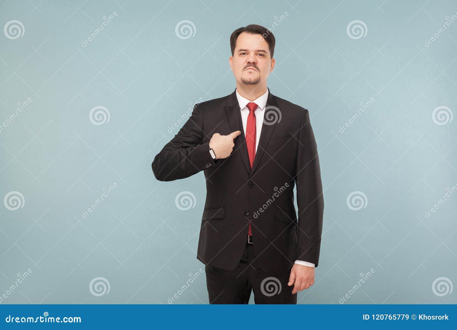 Mann in der klassischen Abnutzung auf Kamera zeigend