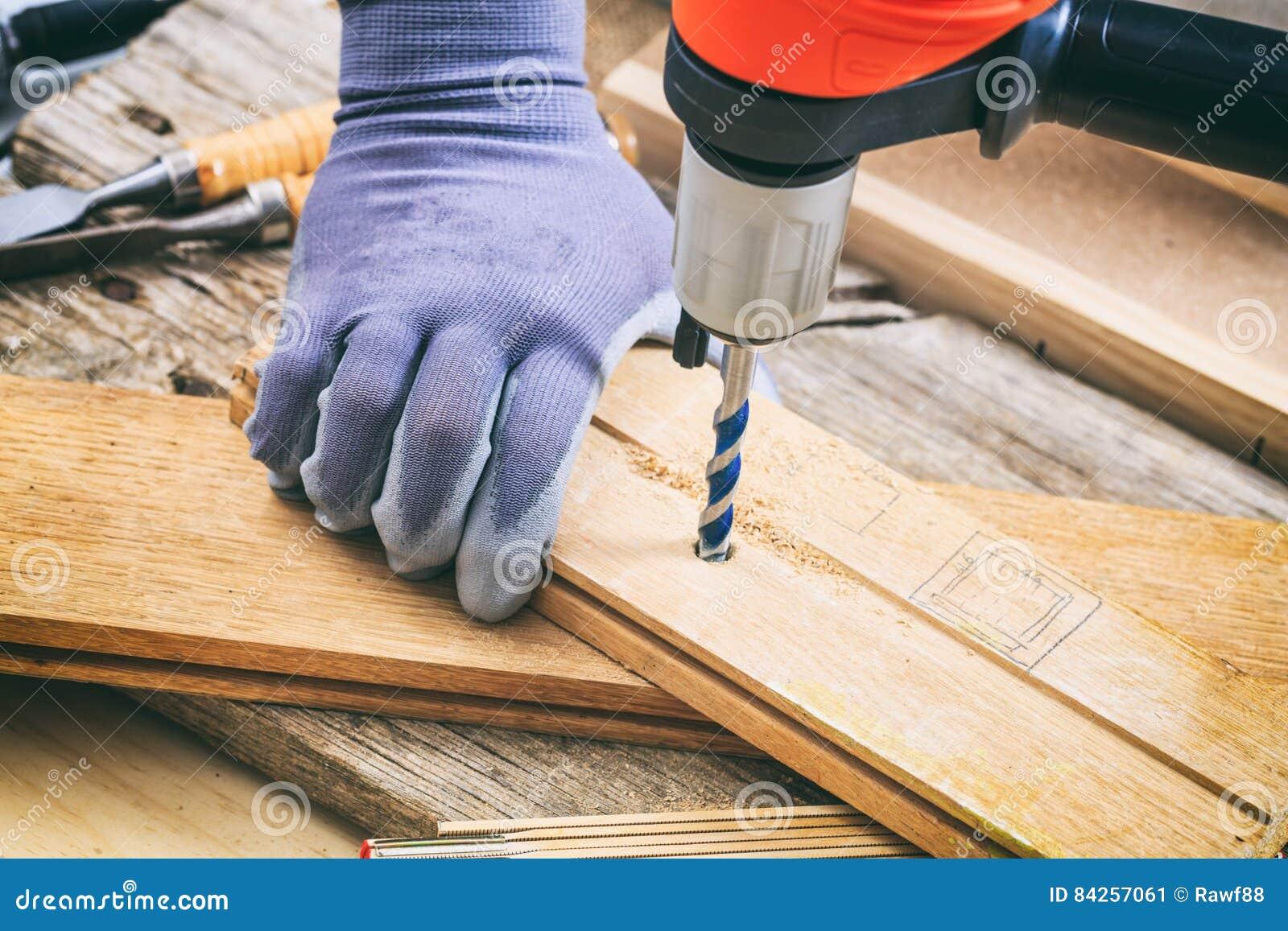 Mann, der mit einem Bohrgerät arbeitet