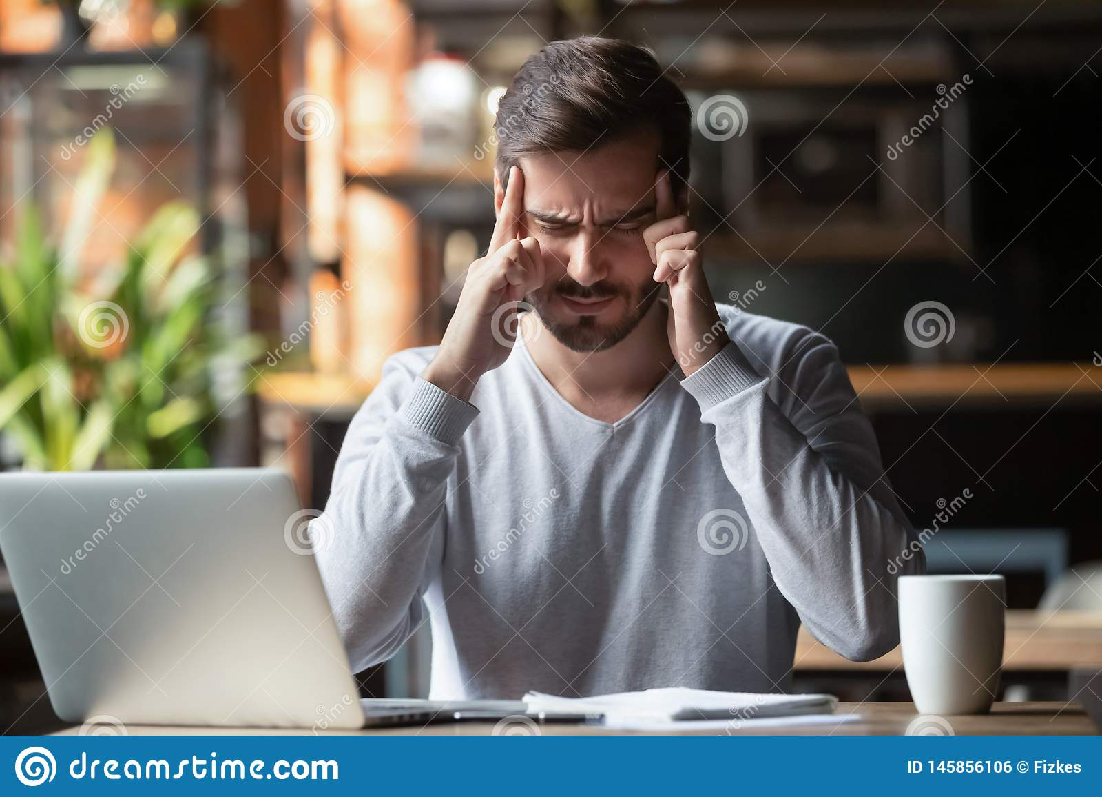Mann, der mit der Fingerstirn denkt oder leidet unter Kopfschmerzen sich berührt