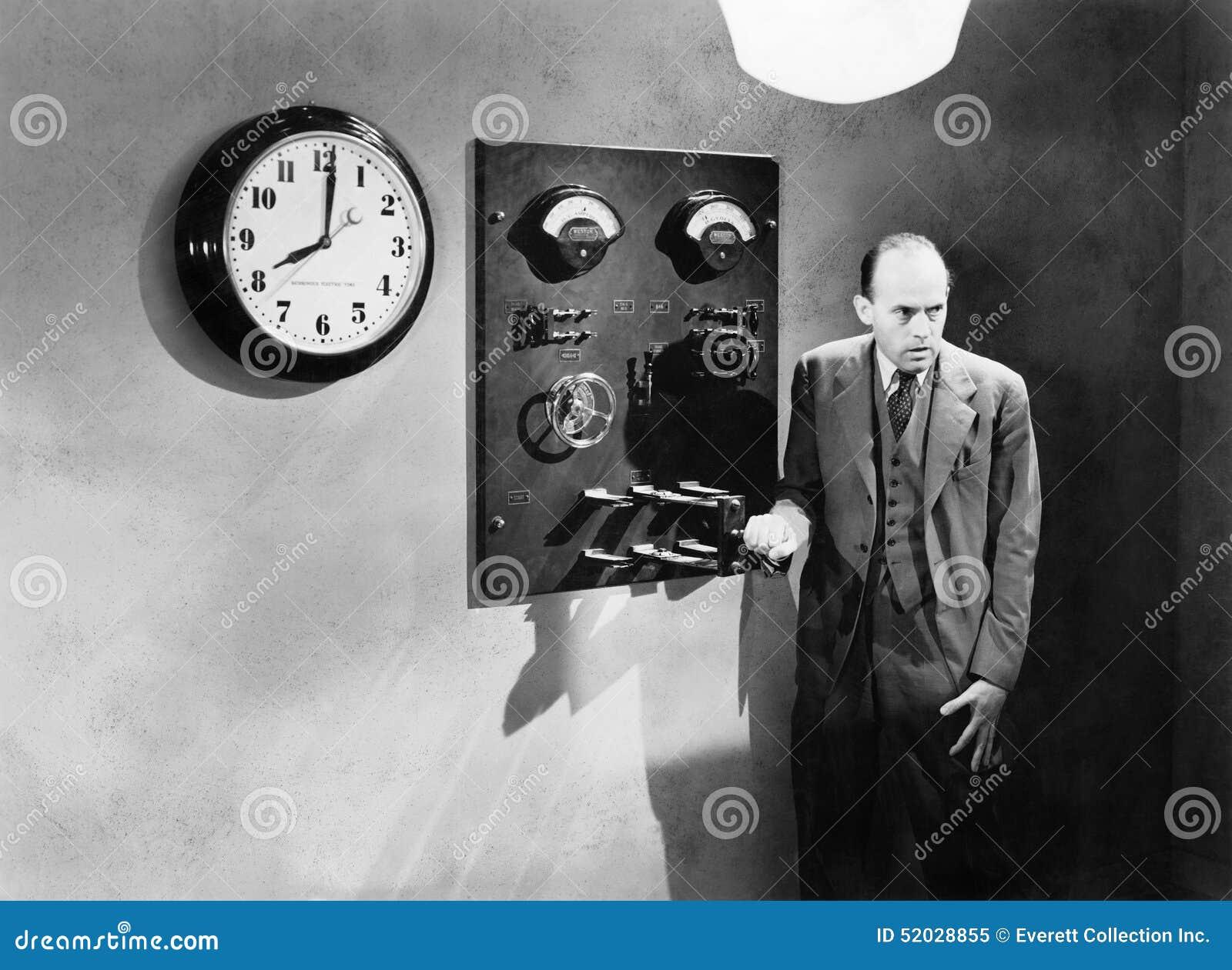 Mann, der nahe bei einem elektrischen Schalter steht (alle dargestellten Personen sind nicht längeres lebendes und kein Zustand e