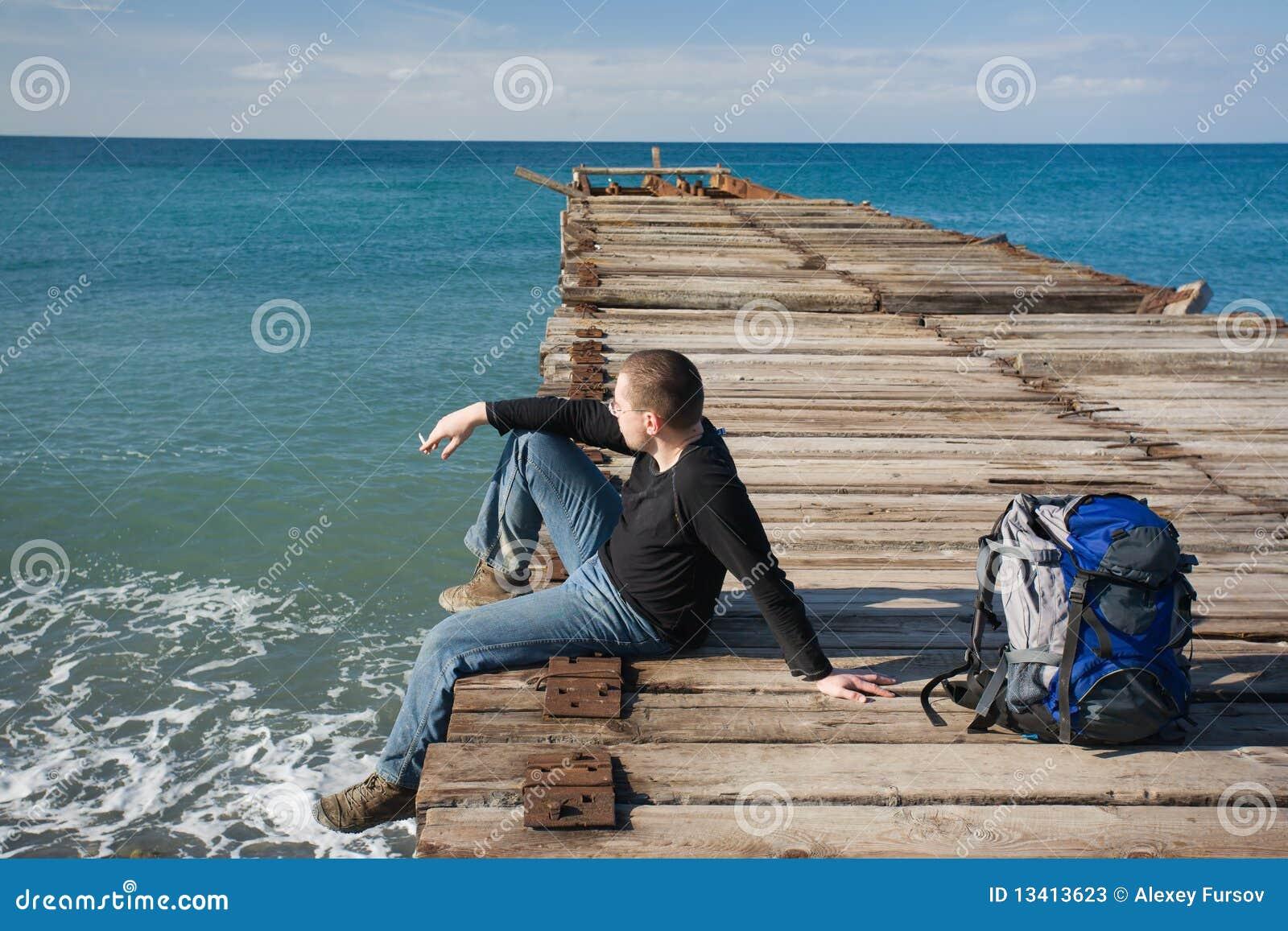 Mann, der am Pier sitzt