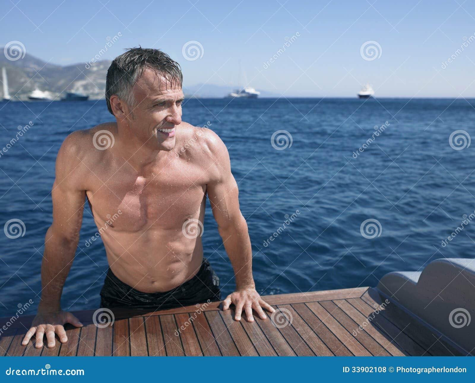 Fußboden Yacht ~ Mann der am rand des fußbodenbrettes der yacht sich lehnt stockfoto