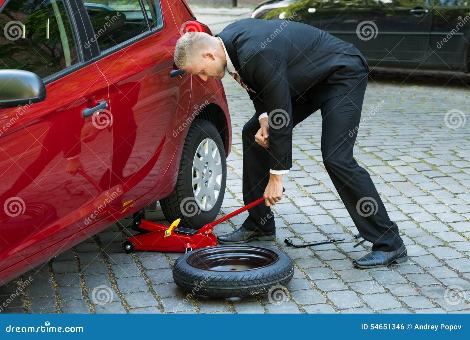 Mann, der roten hydraulischen Wagenheber für die Autoreparatur verwendet