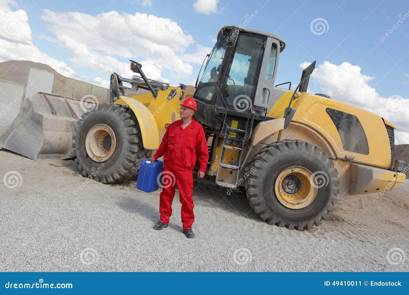 Download Mann In Der Roten Uniform Mit Treibstoffdose, Planierraupe Im Hintergrund Stockbild - Bild von überprüfung, hintergrund: 49410011
