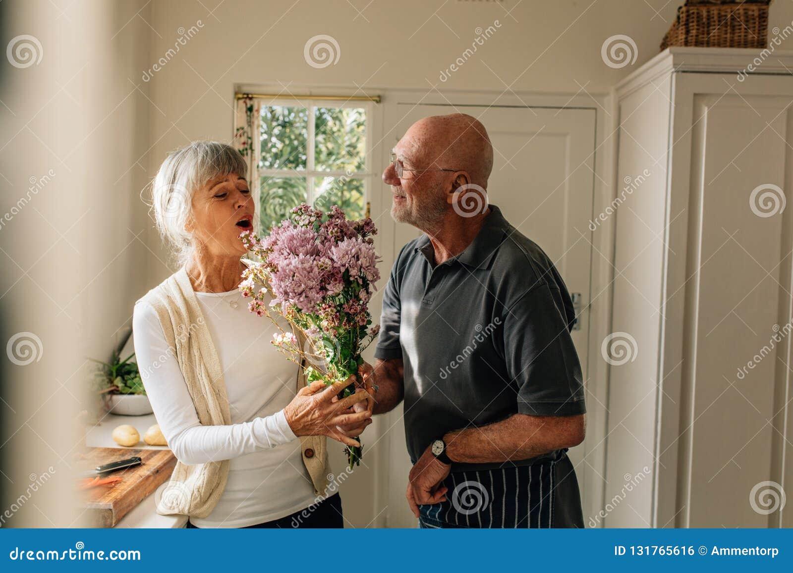 Mann, der seine Liebe für seine Frau zu Hause gibt ihr einen Blumenstrauß ausdrückt Ältere Frau glücklich, ihren Ehemann zu sehen