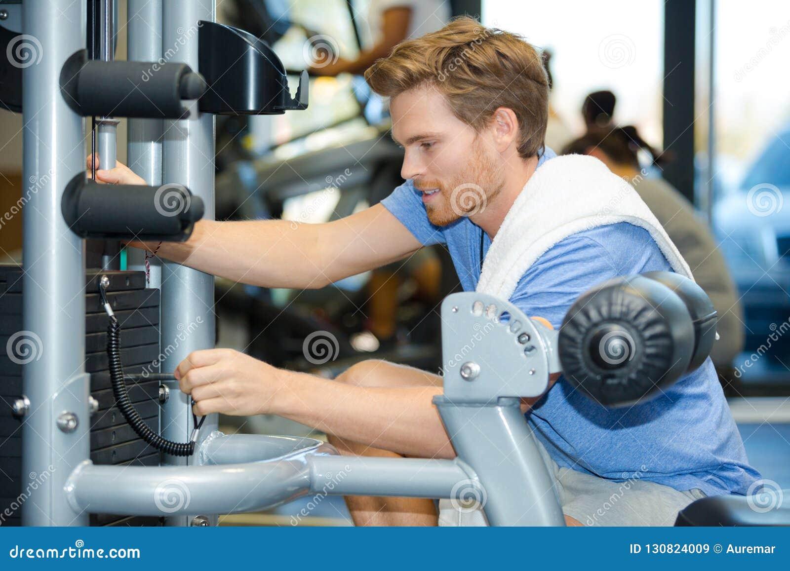 Mann, der Stift in Position bringt, um Gewichte auf Übungsmaschine vorzuwählen