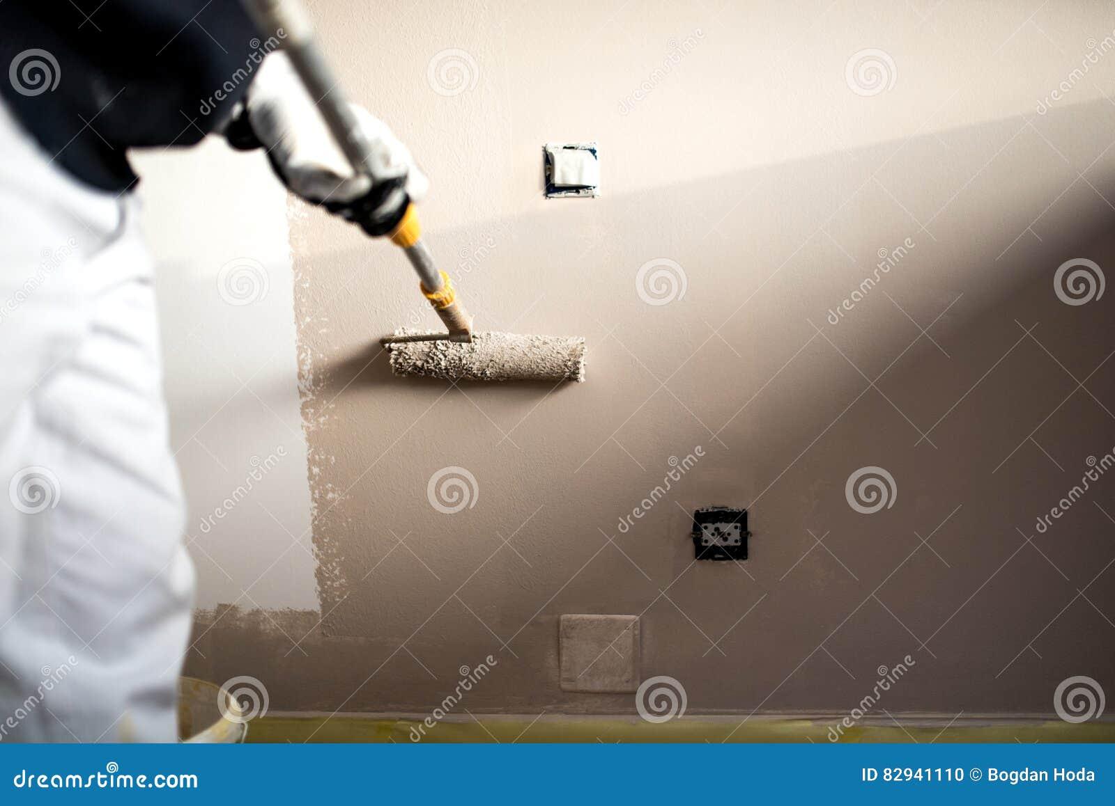 Mann, der Wände mit Farbe verziert Baugips-Arbeitskraftmalerei und Erneuerung mit Berufswerkzeugen