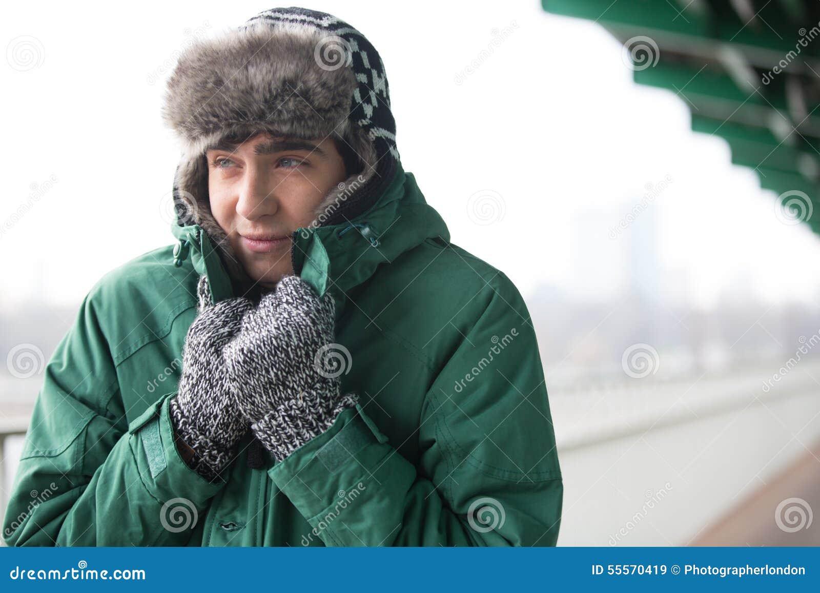 Mann in der warmen Kleidung, die draußen zittert