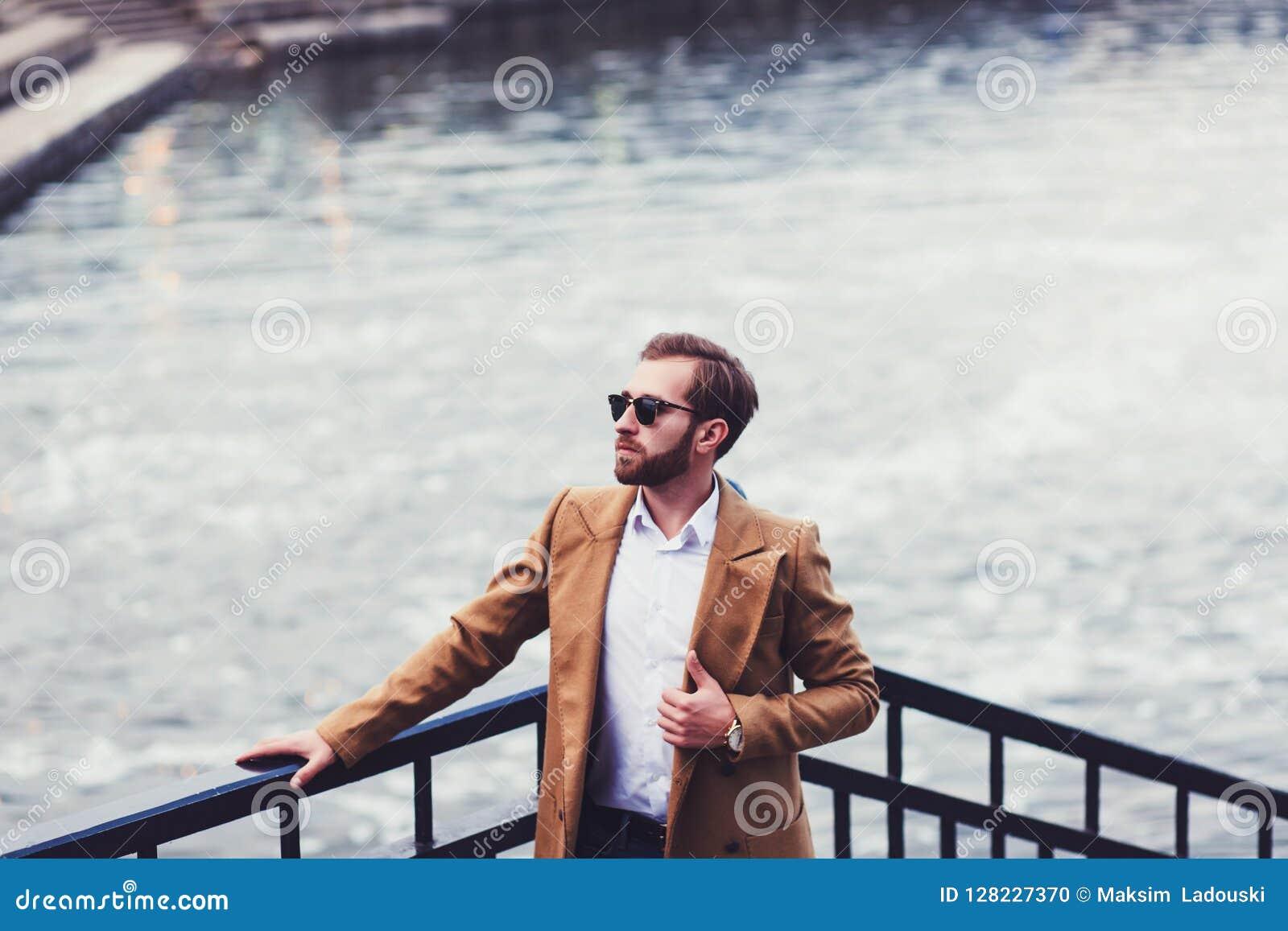 Mann in einem hellen Mantel