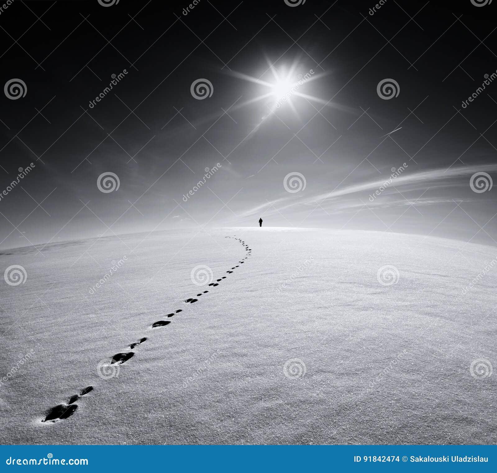 Mann Erde universum Der einsame Mann, der auf Schneekrustenfeld auf der Spur eines Hasen auf dem Hintergrund der Sonne gehen und