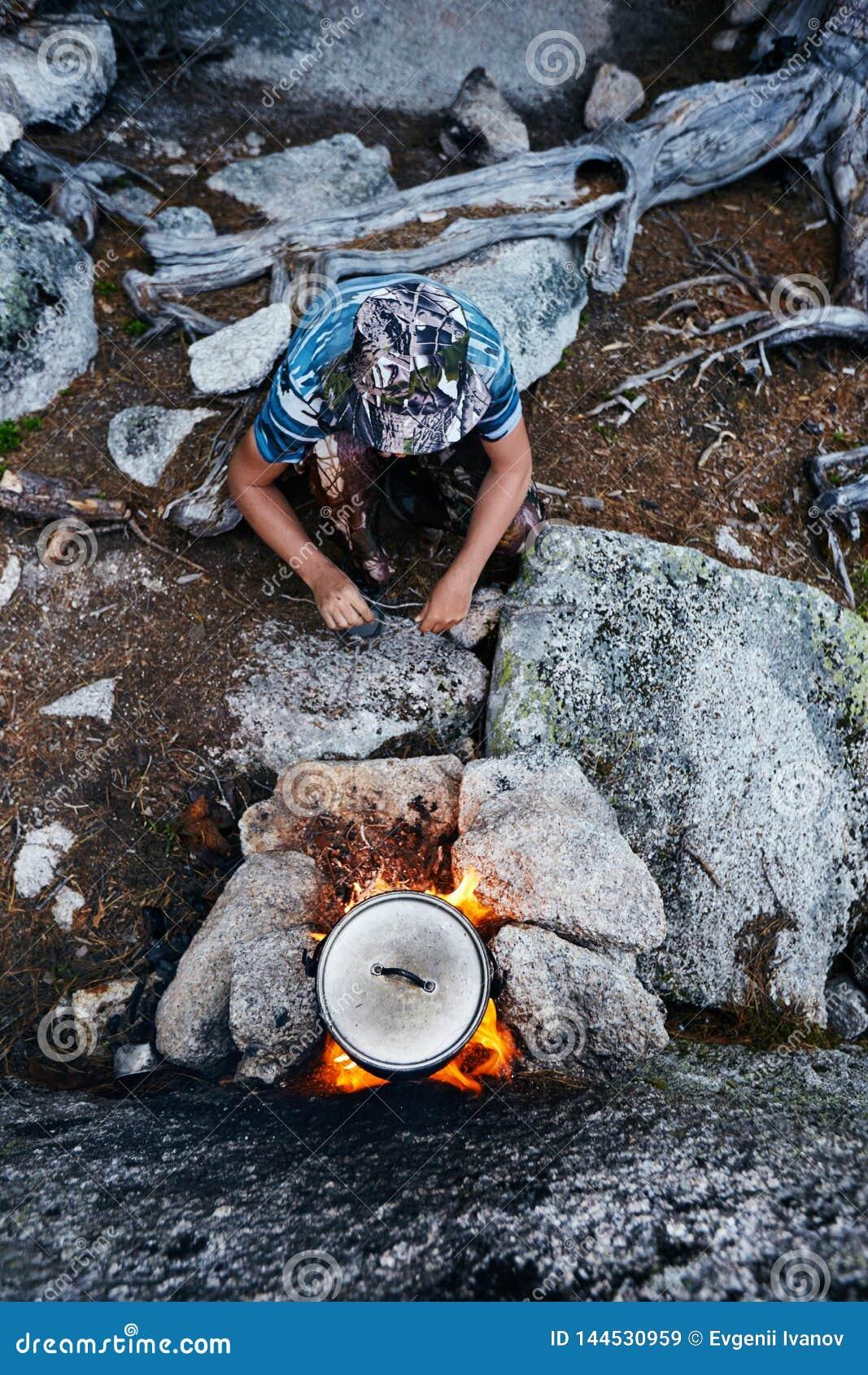 Mann errichtete ein Lagerfeuer im Wald in der Natur Überleben Sie in den Bergen im Wald und in einer Topfwanne über einem Lagerfe