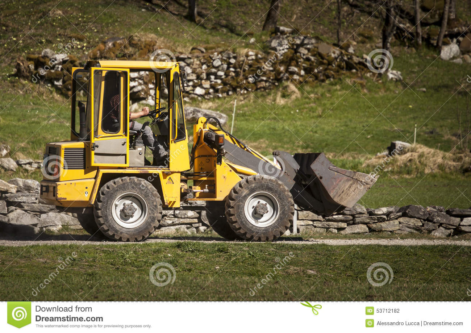 Mann fährt gelben Baggerlader