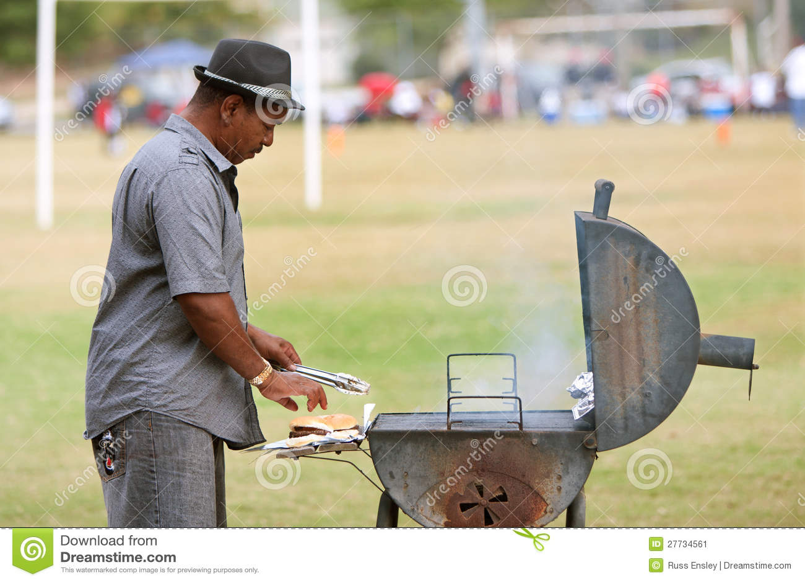 Mann grillt Hamburger für Jugend-Fußballspiel