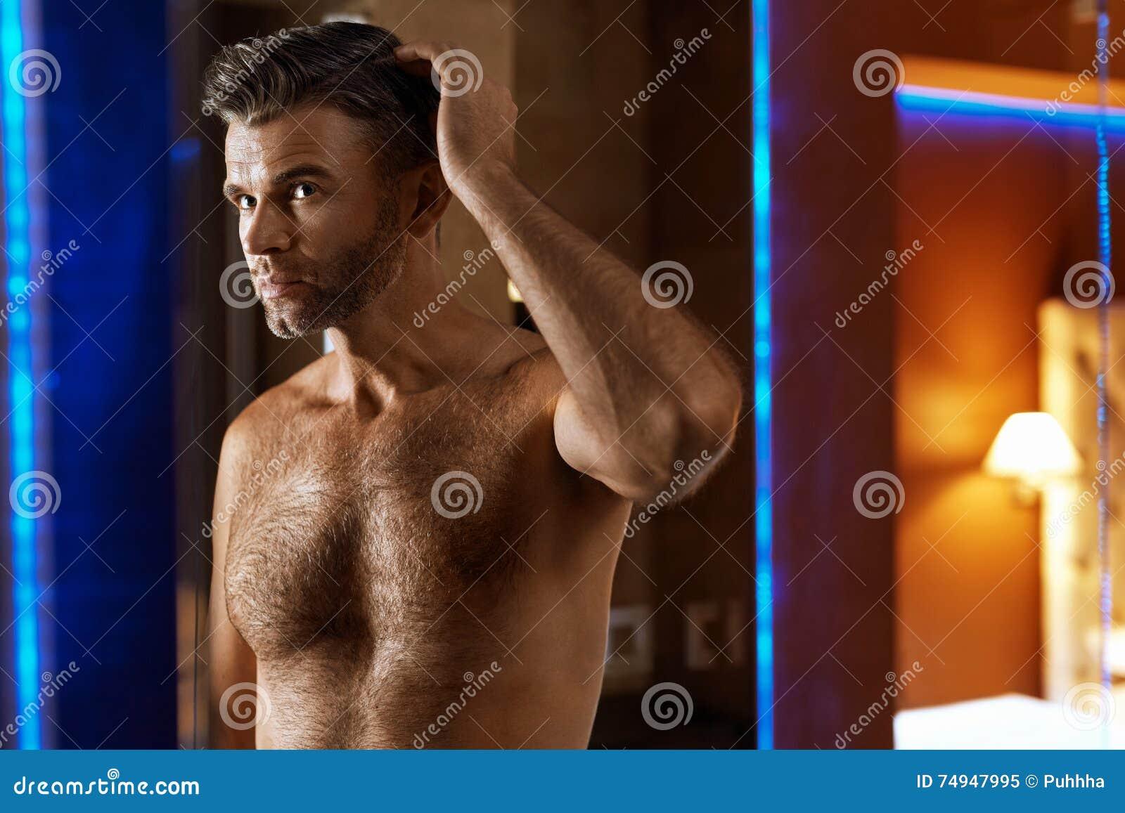 Mann-Haarpflege Gut aussehender Mann, der sein Haar berührt Mann-Pflegen