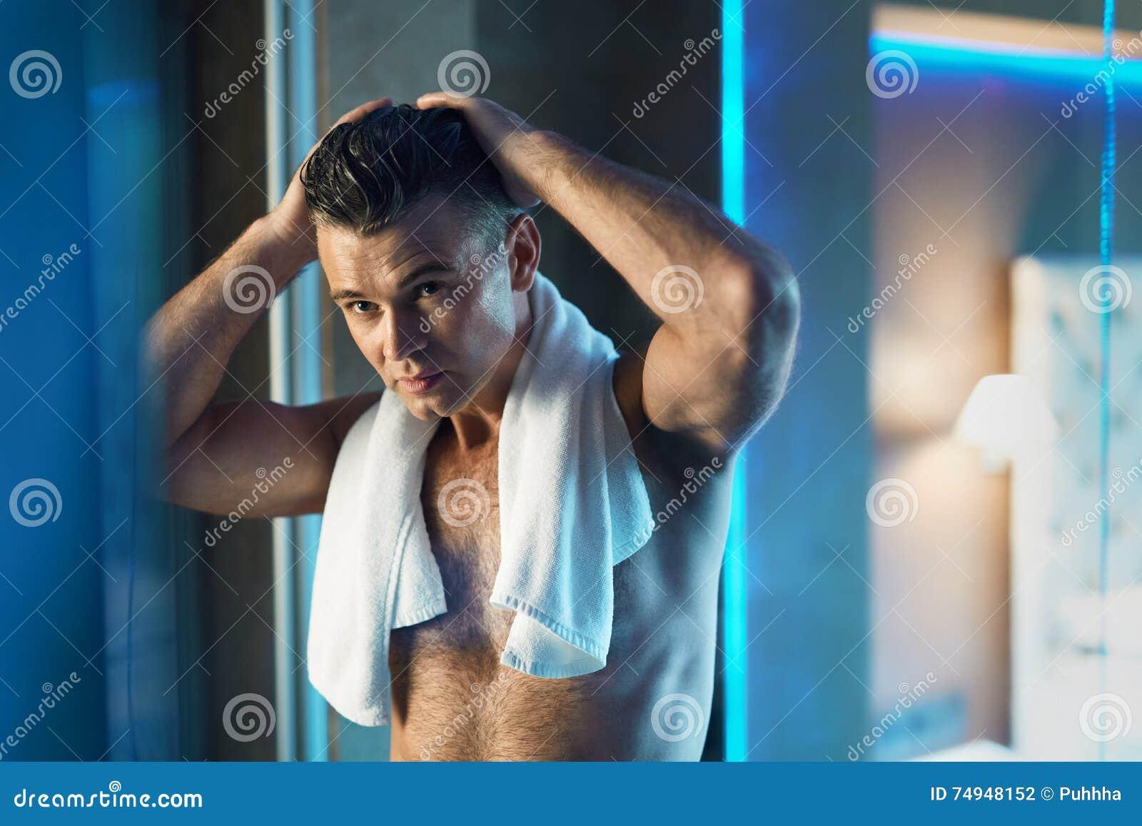 Mann-Haarpflege Mann, der sein Haar im Badezimmer berührt Mann-Pflegen
