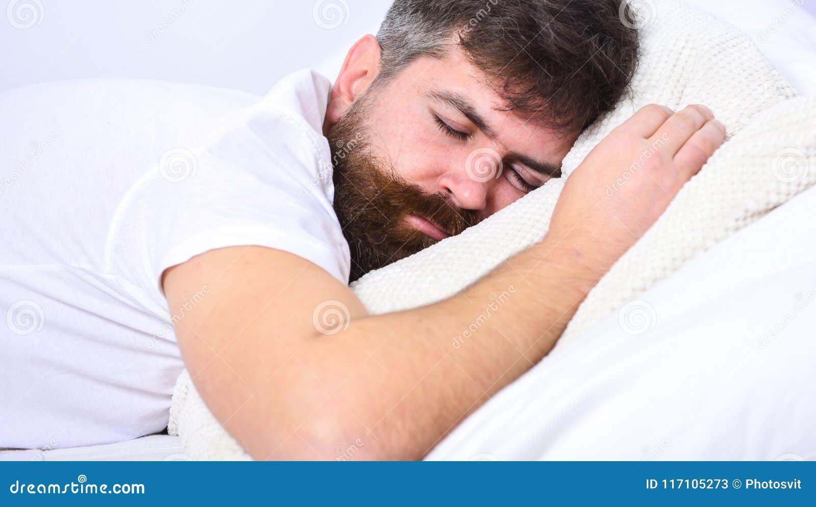 Mann im Hemd, das auf Bett, weiße Wand auf Hintergrund legt Macho mit Bart und Schnurrbart, die, entspannend schlafen und haben H