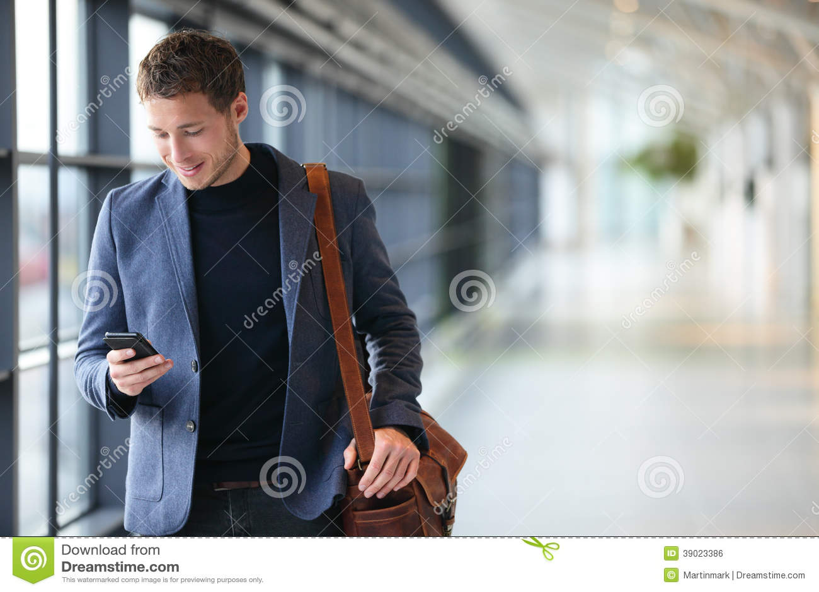 Mann am intelligenten Telefon - junger Geschäftsmann im Flughafen