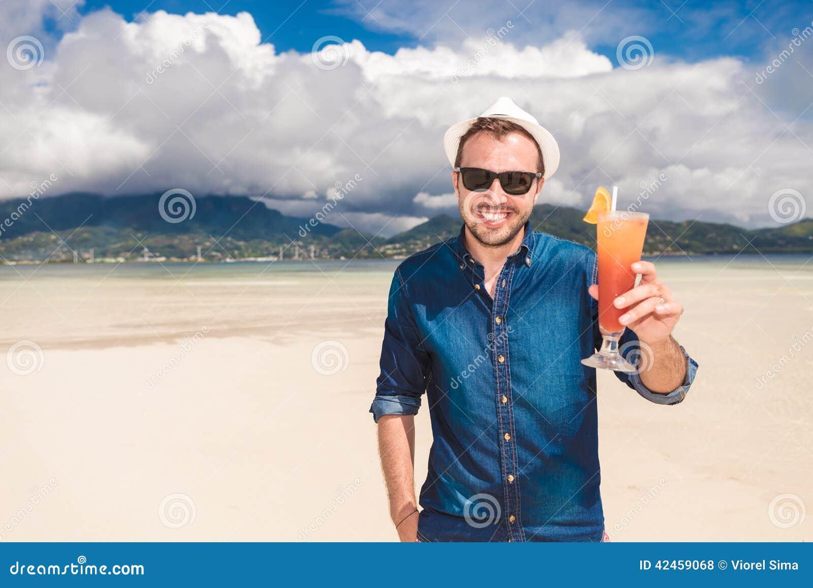 Mann lädt Sie zu einem kalten Getränk auf dem Strand ein