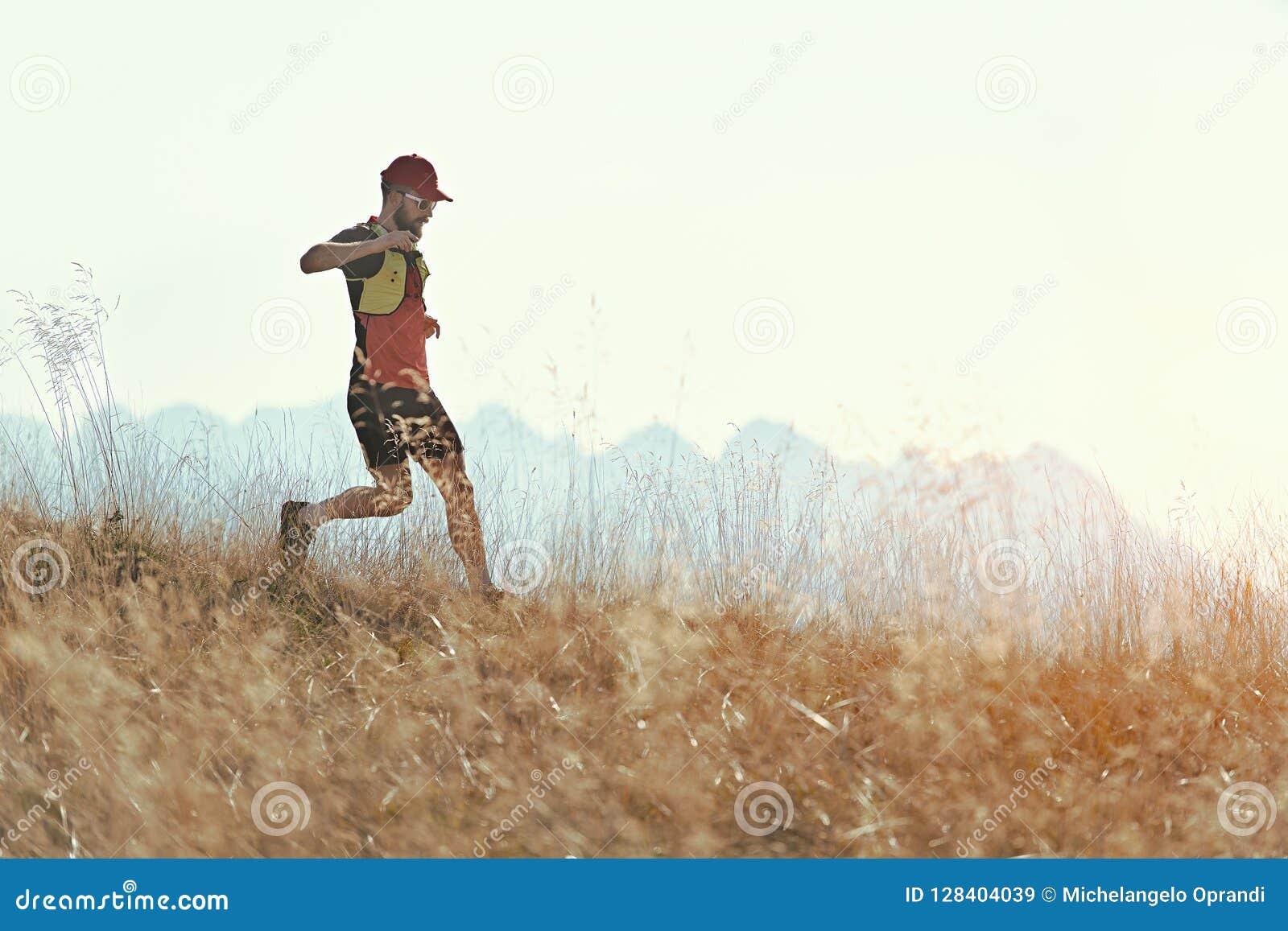 Mann läuft abwärts unter den Herbstbergwiesen